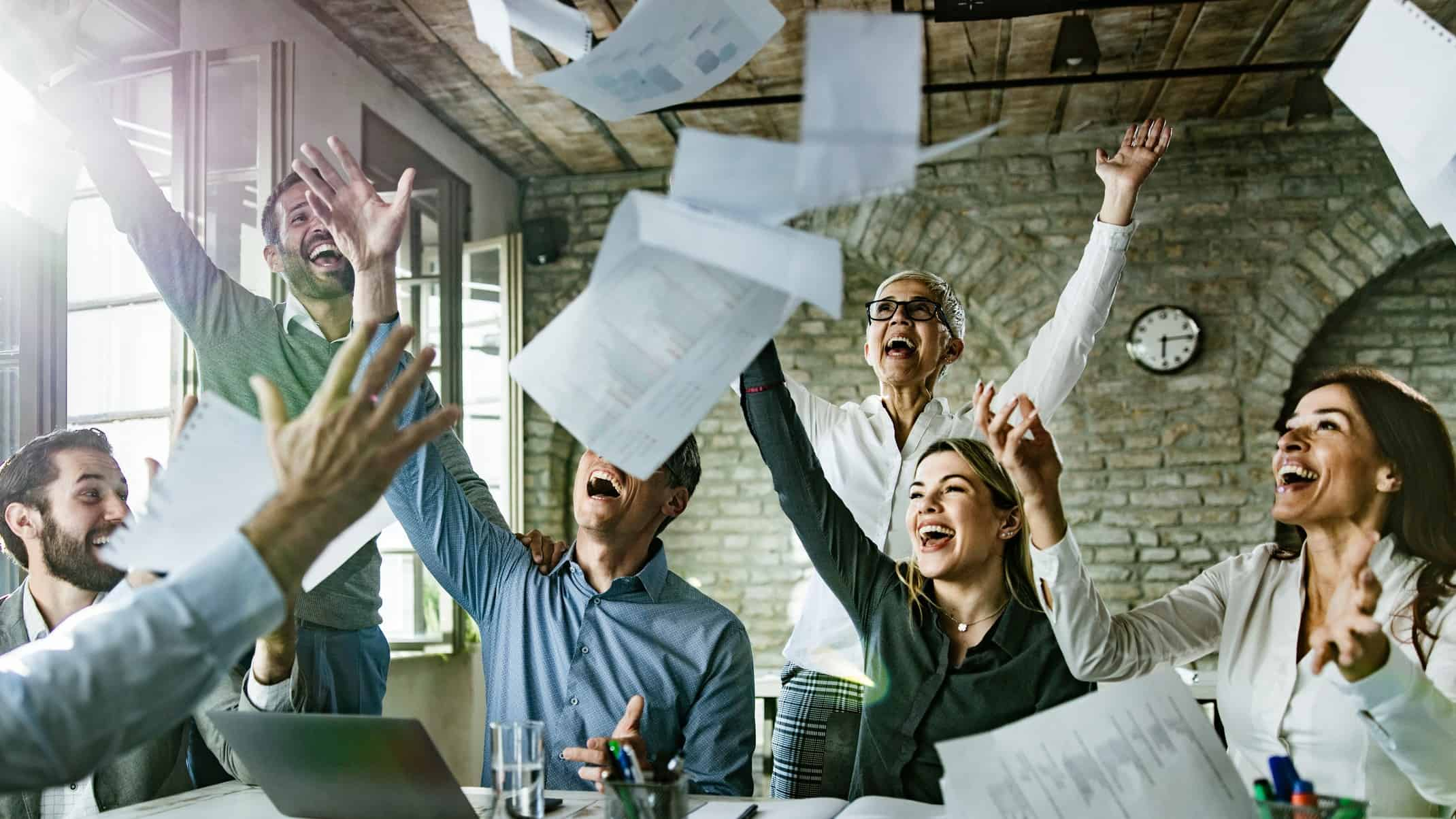 Happy office workers throw reports in the air