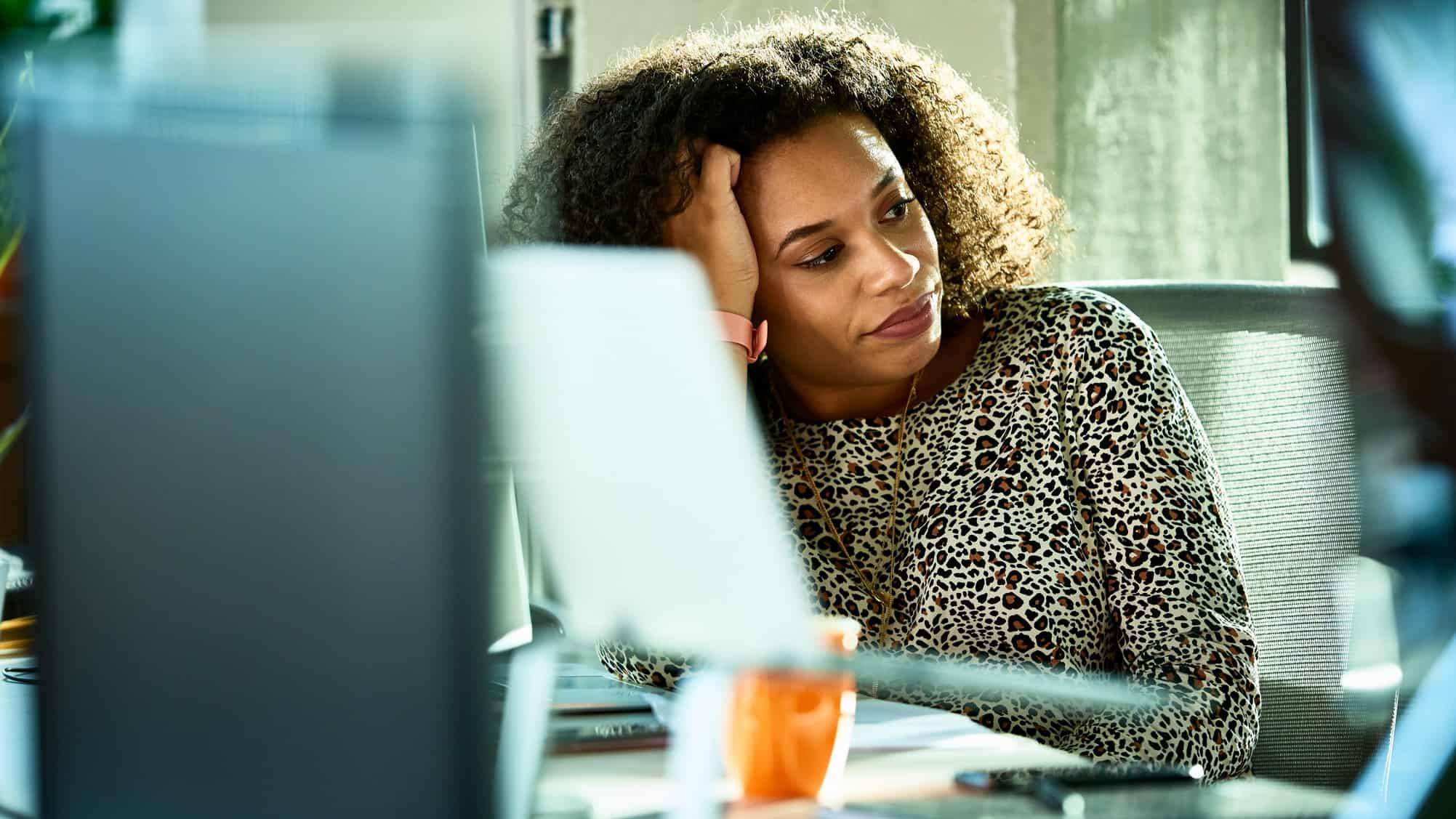 Woman with frustrated expression sits in front of a laptop