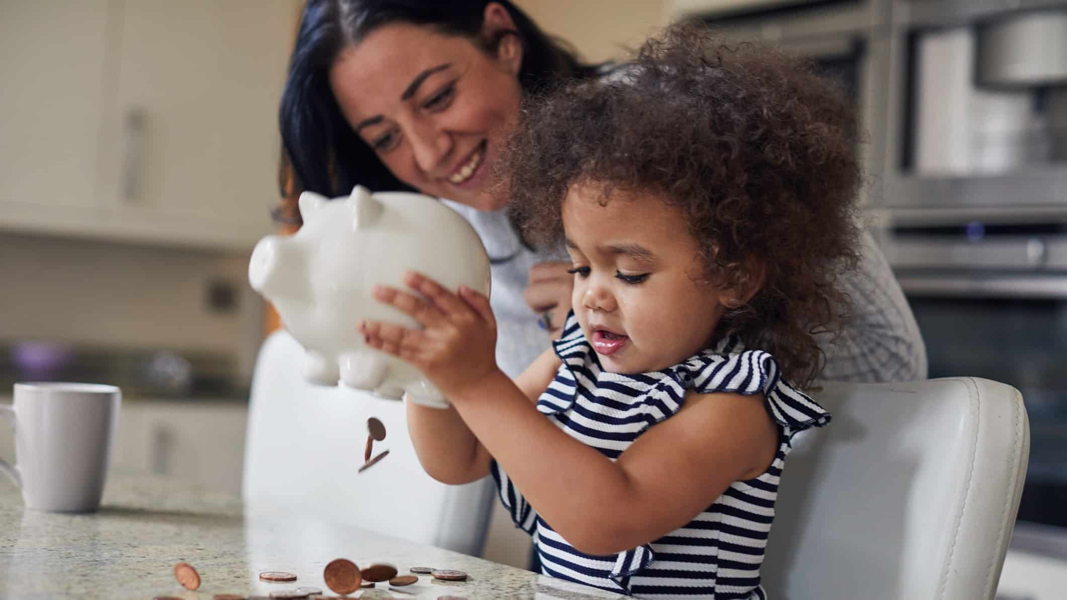 child emptying coins out of savings piggy bank