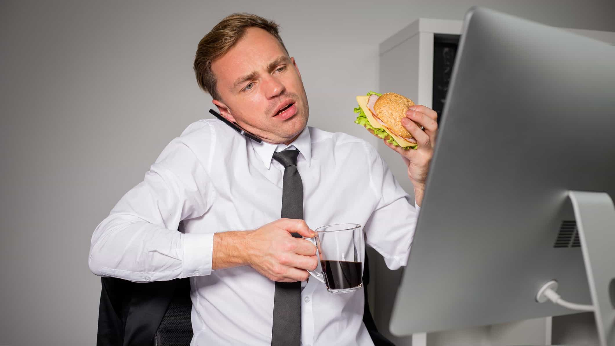 Financial advisor on phone and looking at computer whilst eating and holding coffee