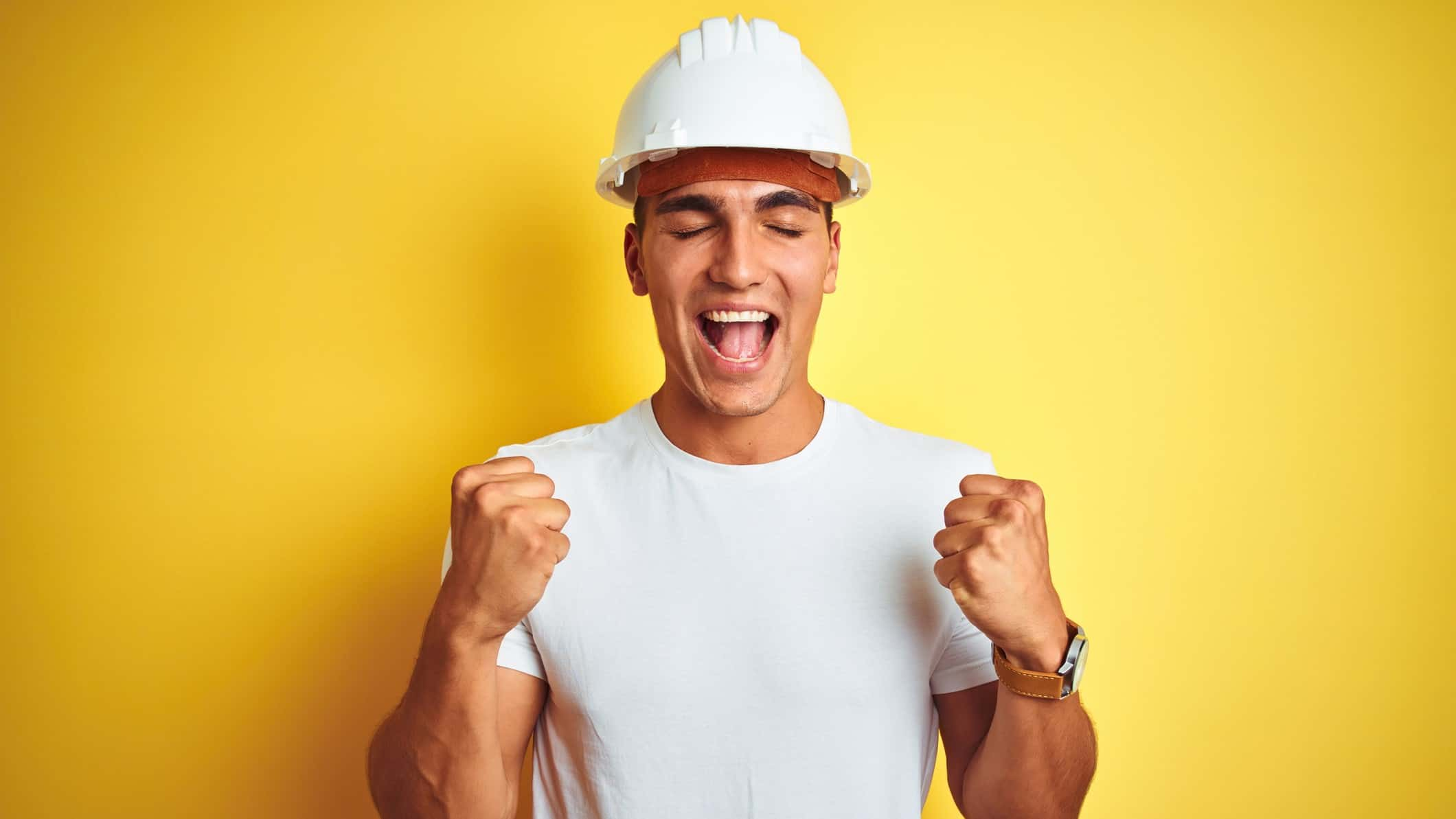 Man in mining hat with fists raised and eyes closed looking happy and excited about some news