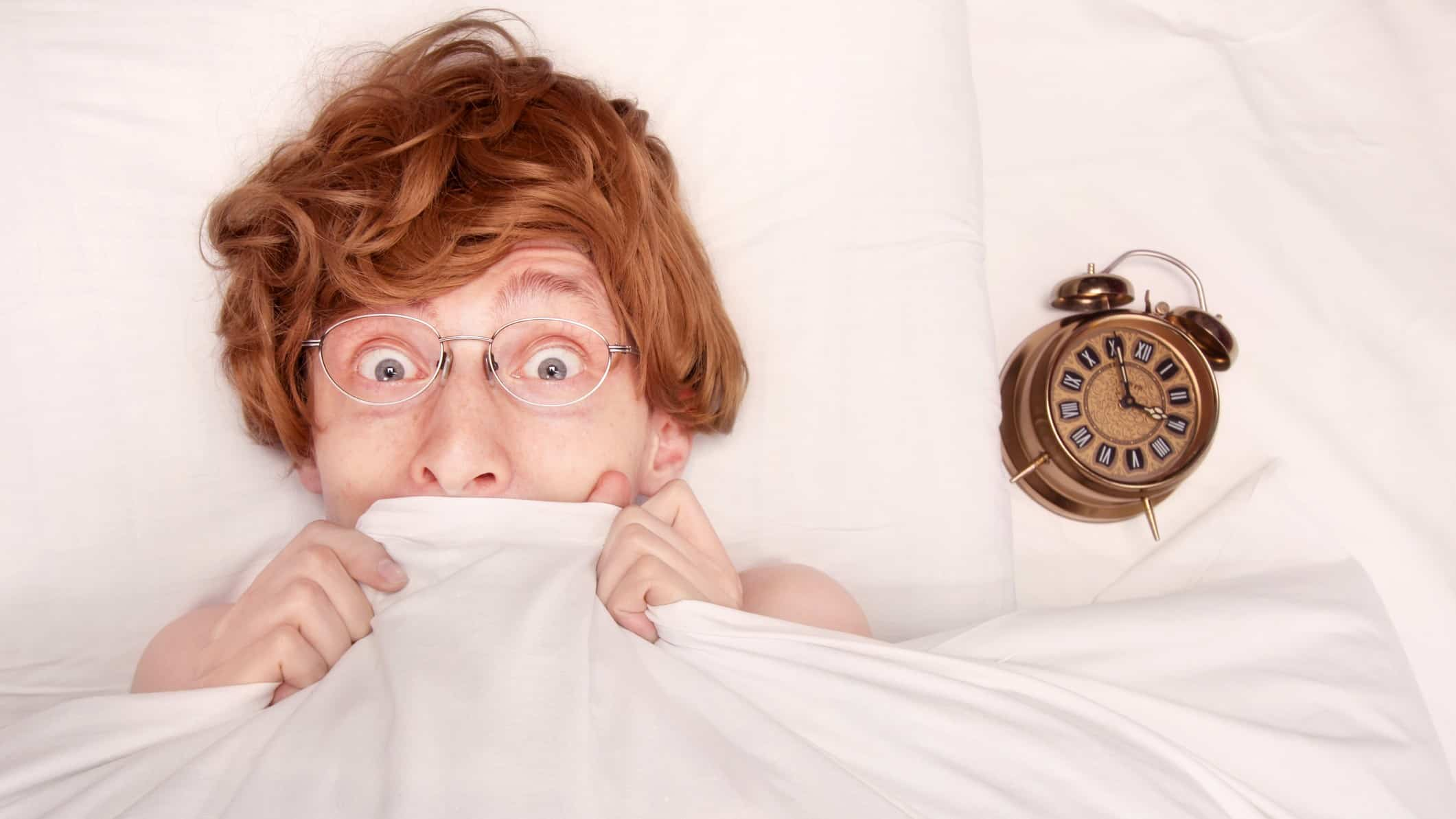 nerdy looking guy with glasses peeking out from under bed sheets