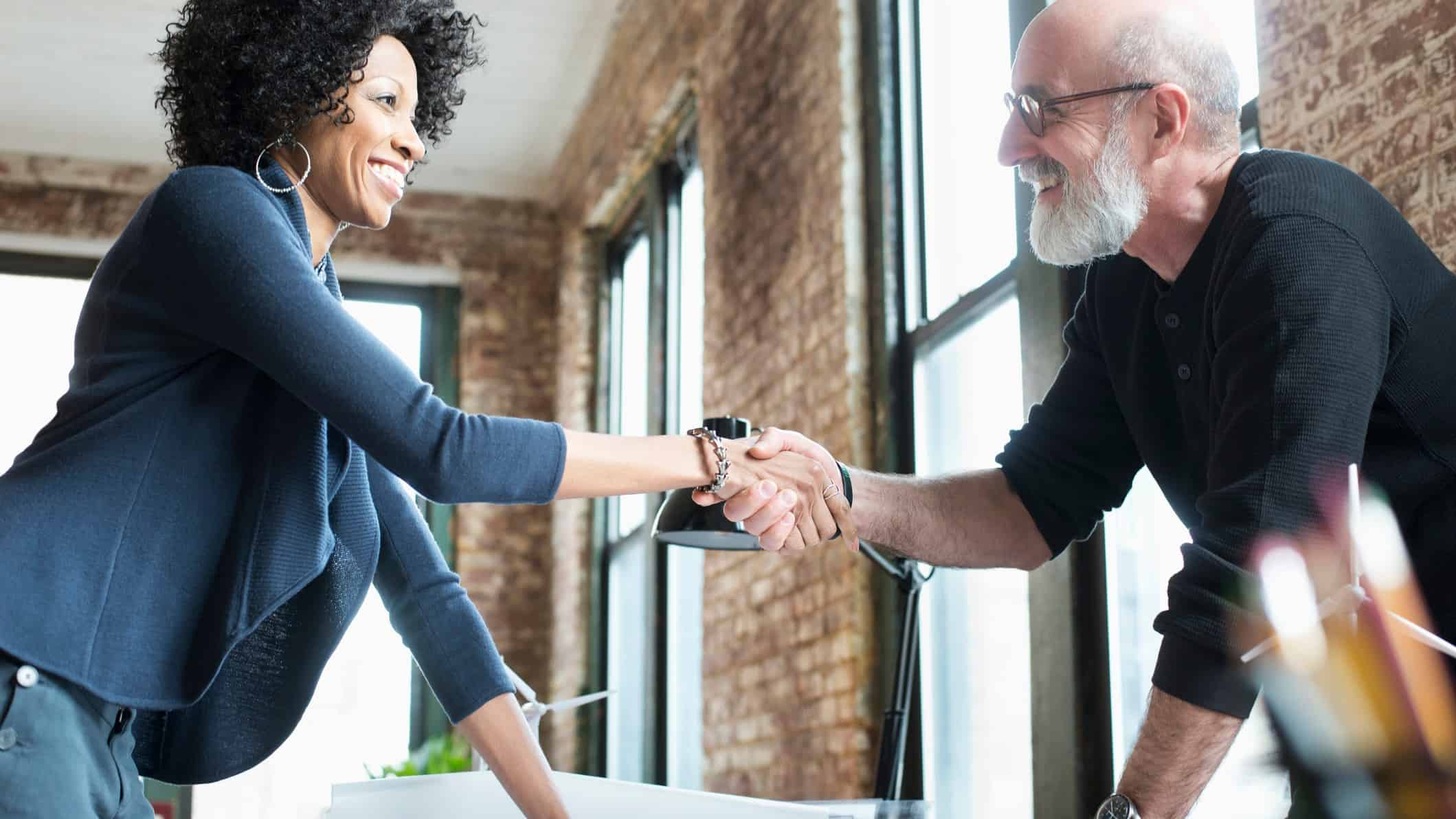 a man and woman agreeing to a deal with a handshake