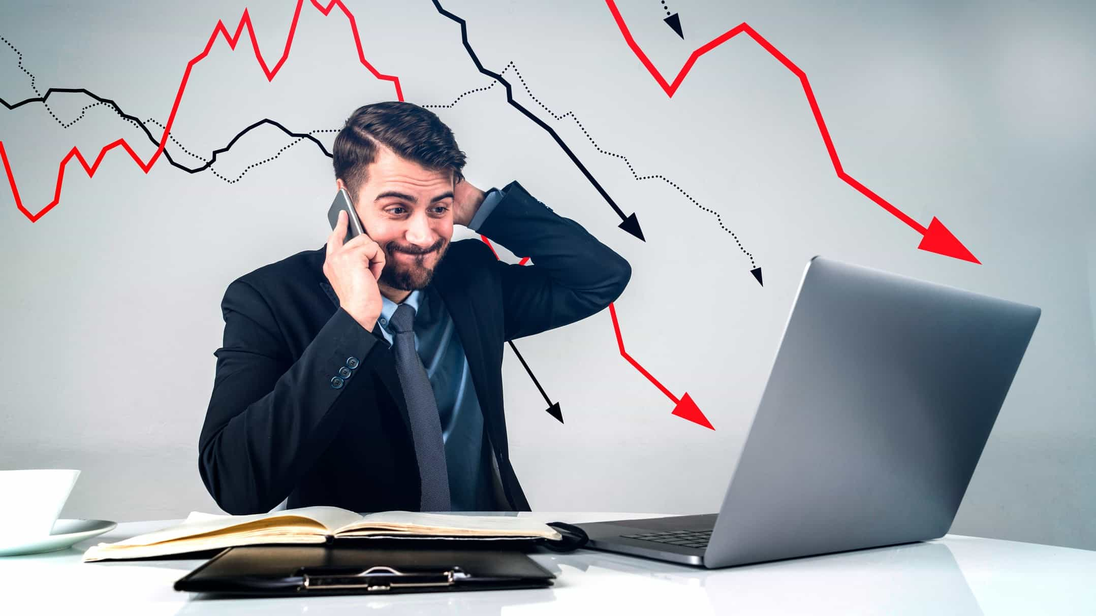 shocked man looking at laptop with declining arrows in the background showing a falling share price