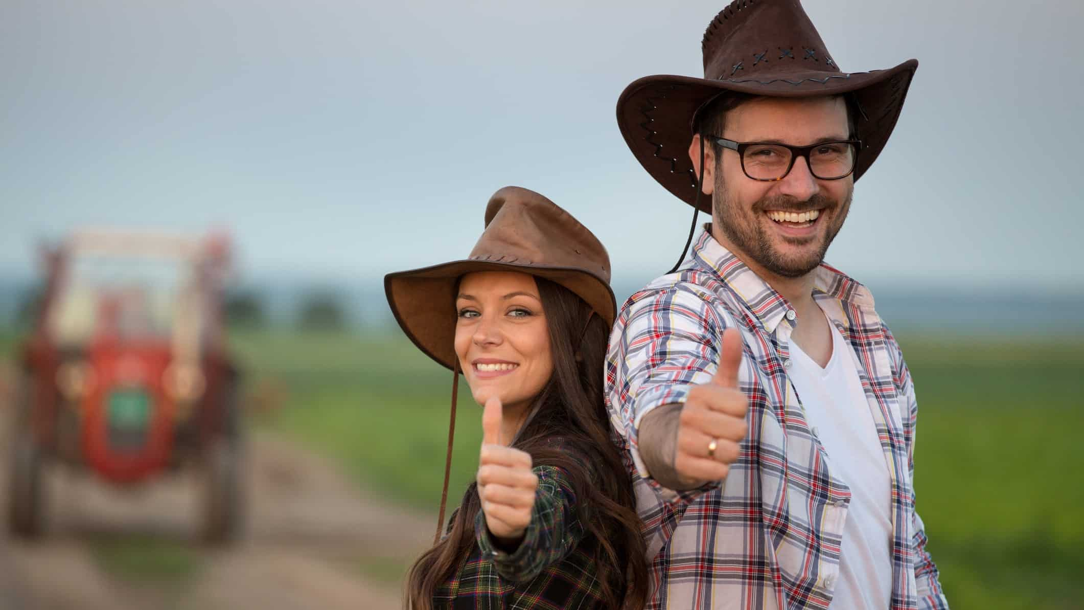 happy farming couple both with their thumbs up