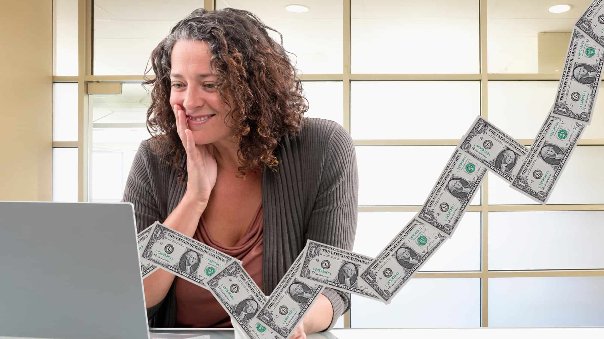 happy woman looking at her laptop with notes of money coming out representing financial success and a rising share price and dividend yield