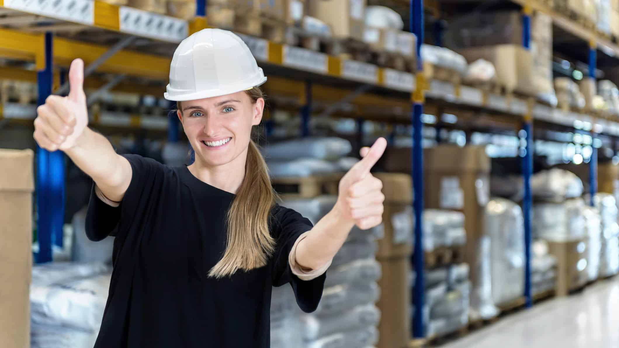 A happy woman in a hard hat gives two thumbs up, standing in a packing warehouse.