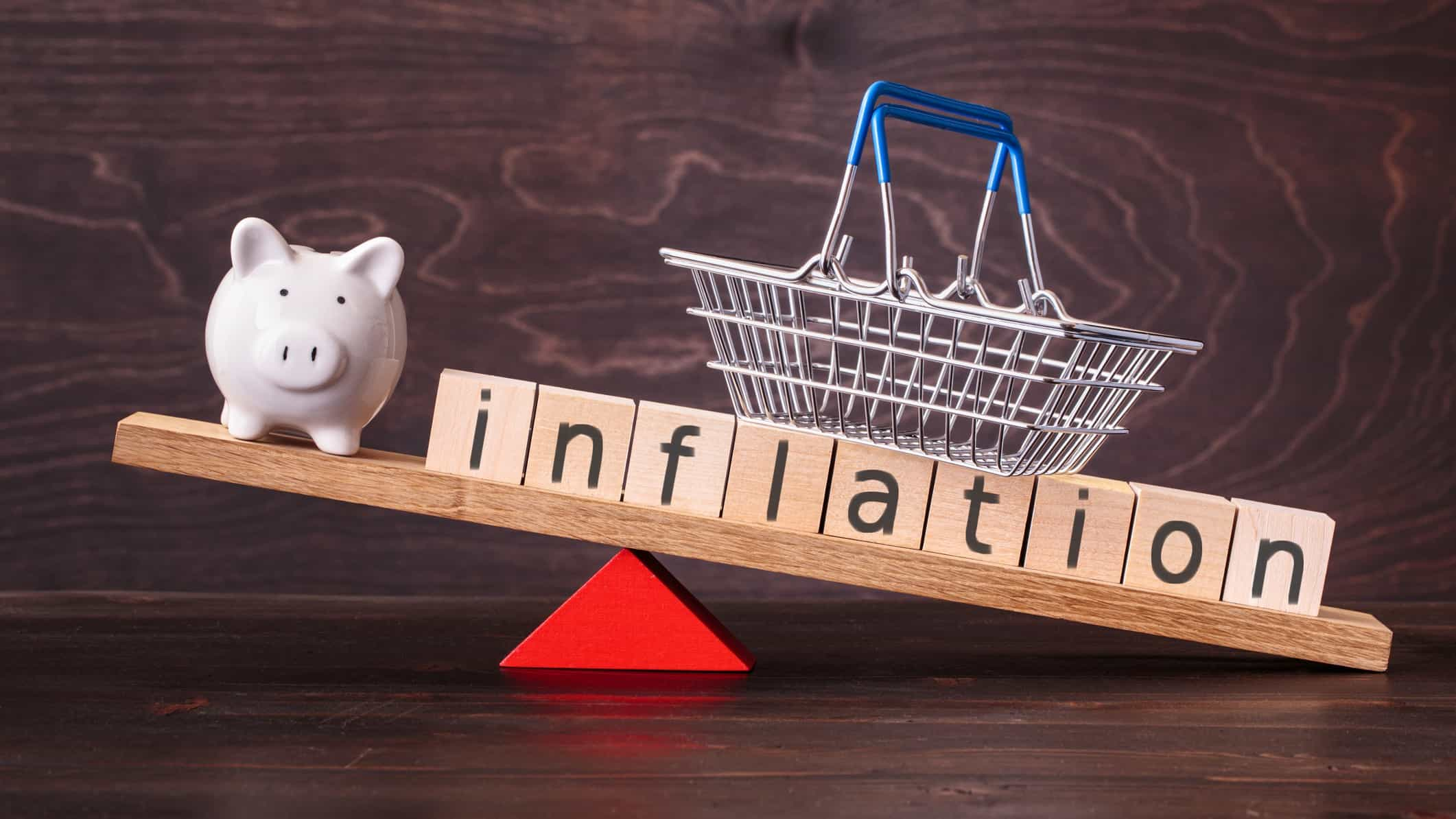 inflation written on wooden cubes being balanced with a piggy bank and small shopping basket
