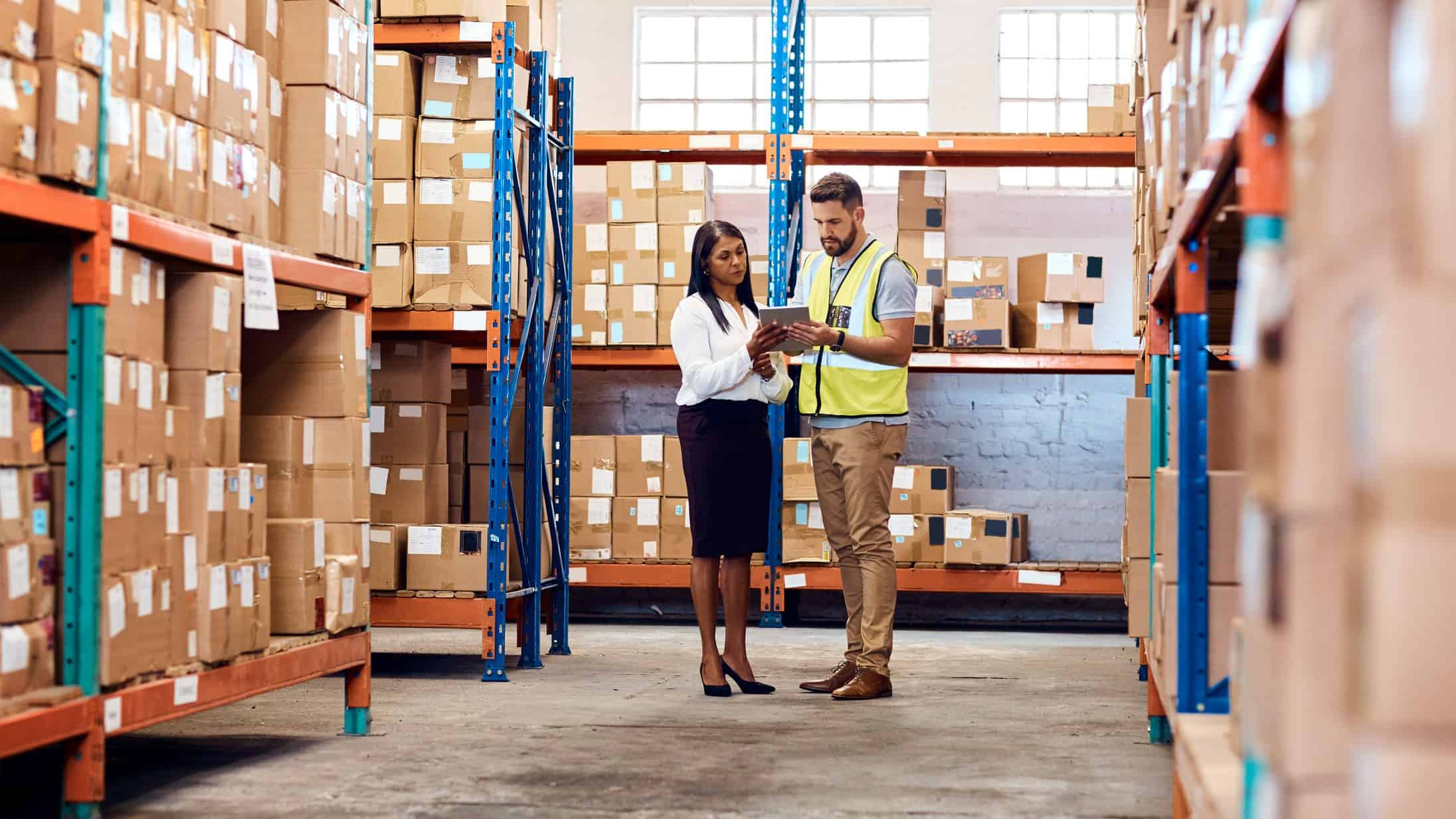 man and woman have a discussion on a tablet in a transportation warehouse