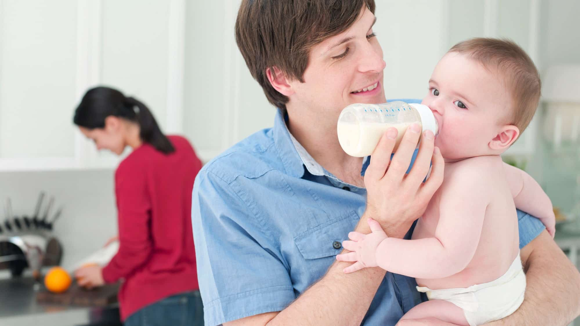happy man feeding baby in the home kitchen