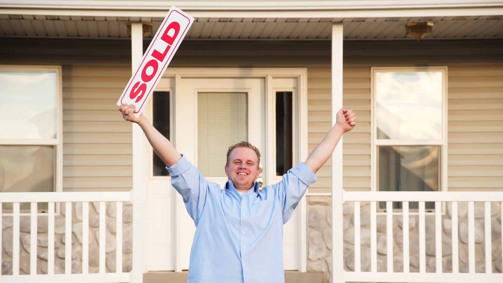 Stockland dividend share price man happy at property being sold with arms raised in the air