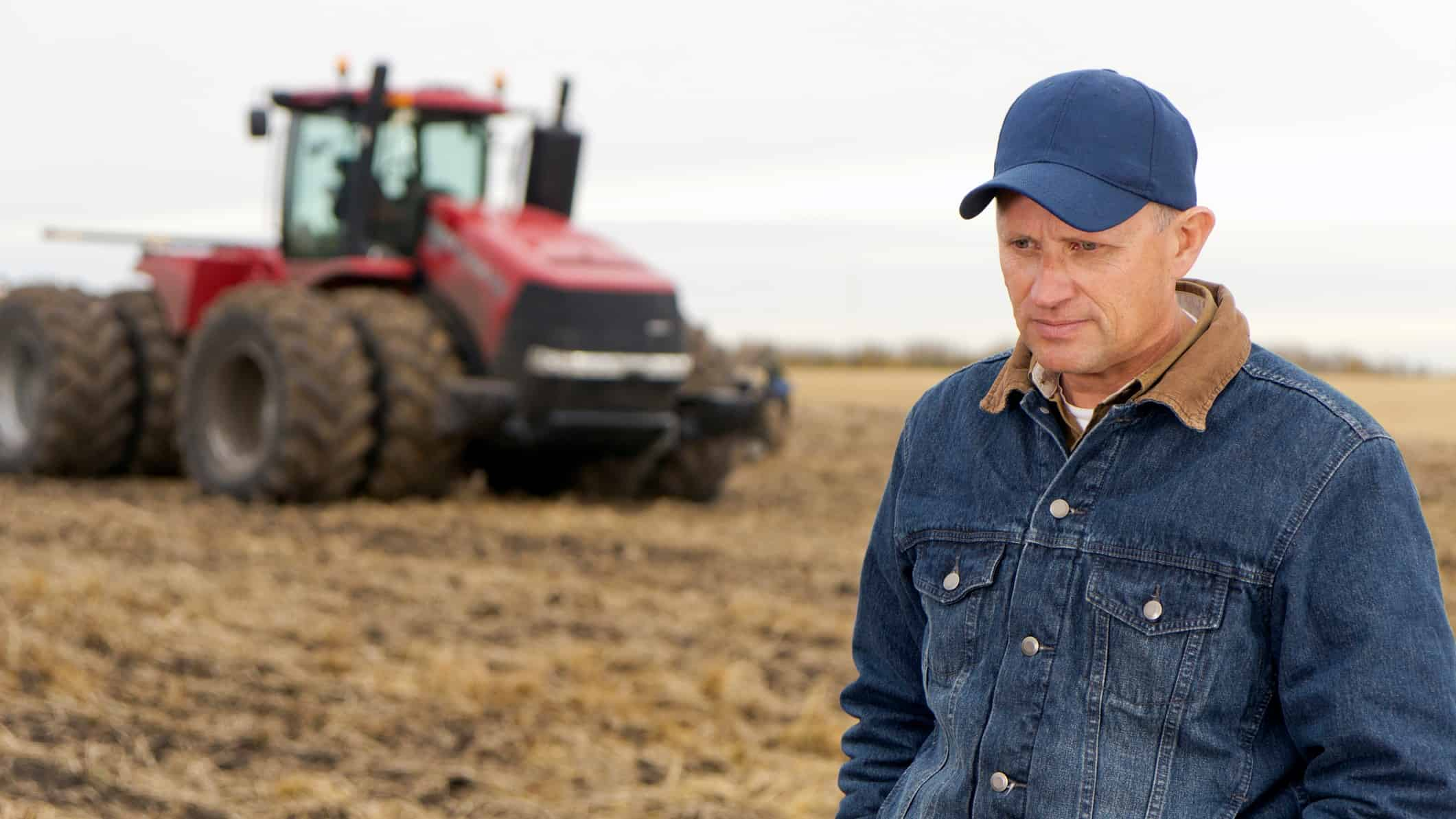 sad and disappointed farmer on a farm with a tractor in the background