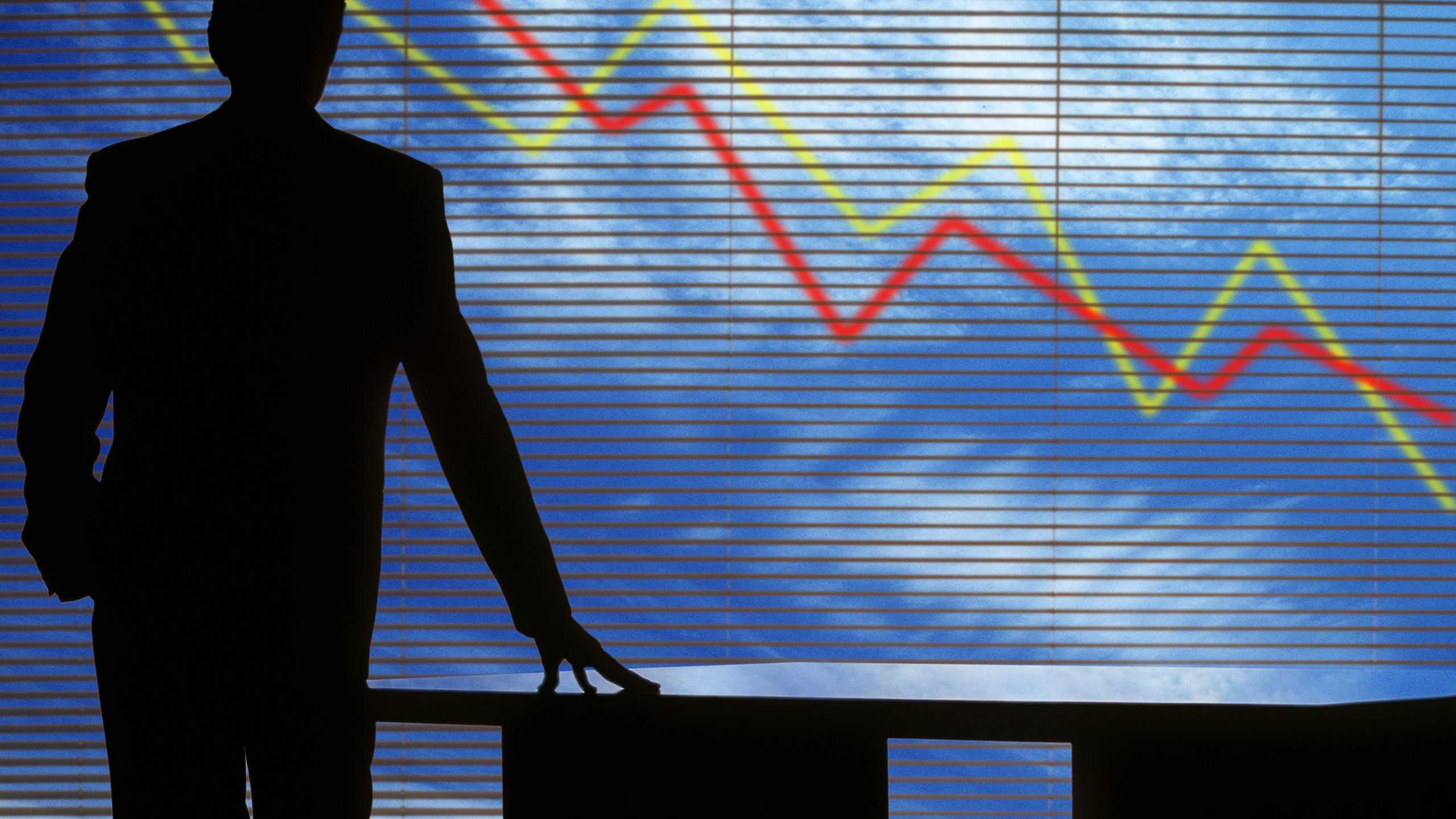 shadow of a man looking out a window with arrows signifying falling share price