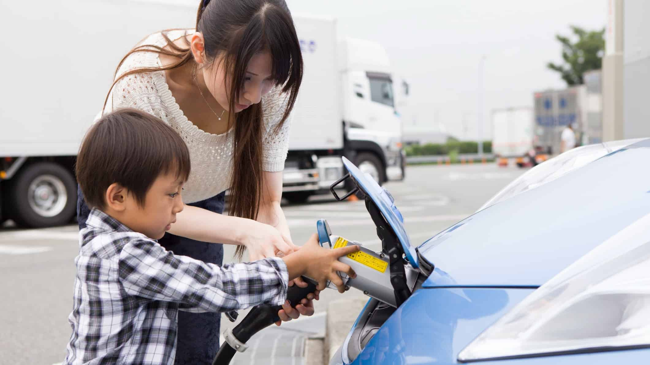 Boy and woman charge electric vehicle