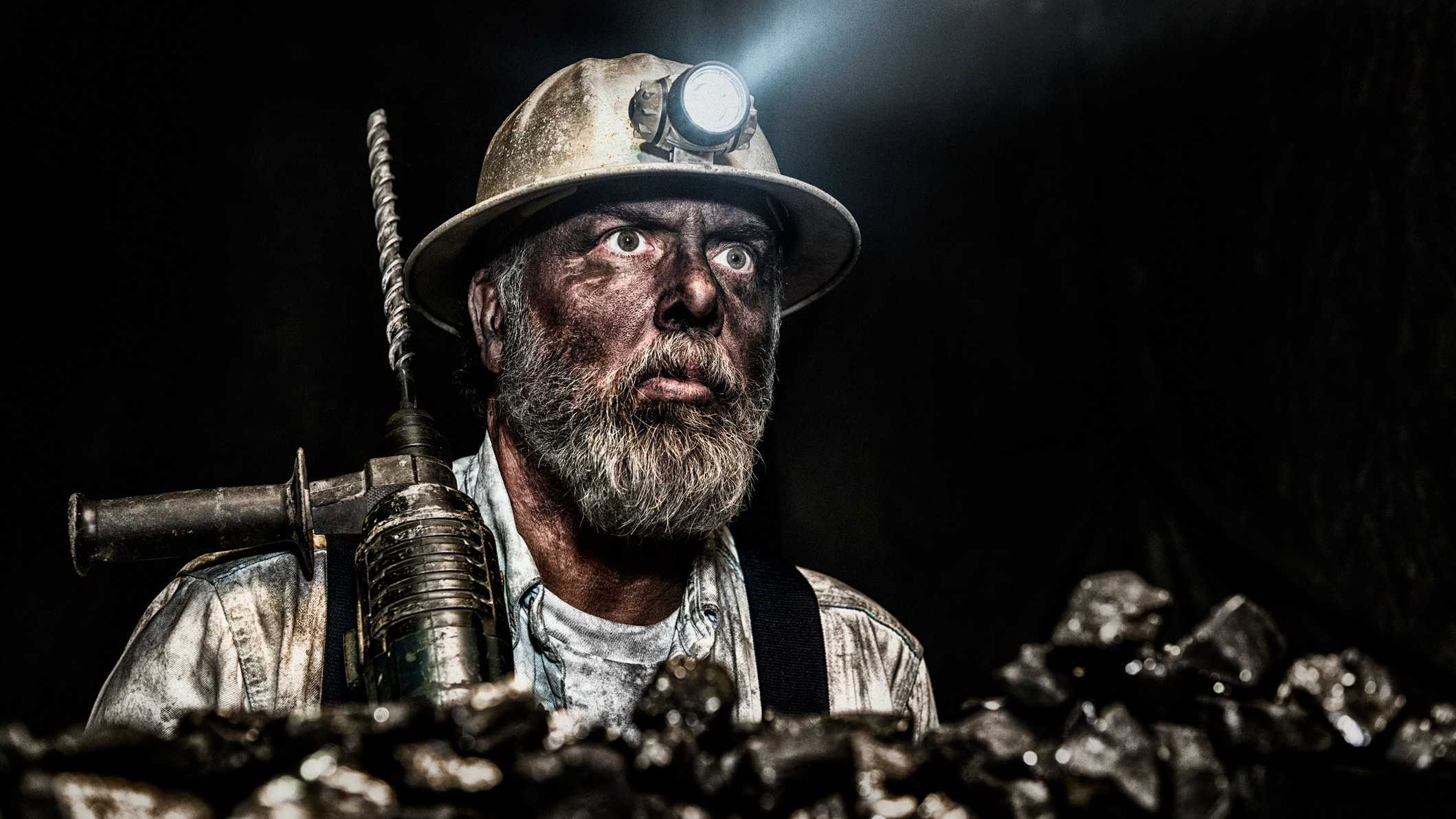 Coal miner with dirty face in a mine