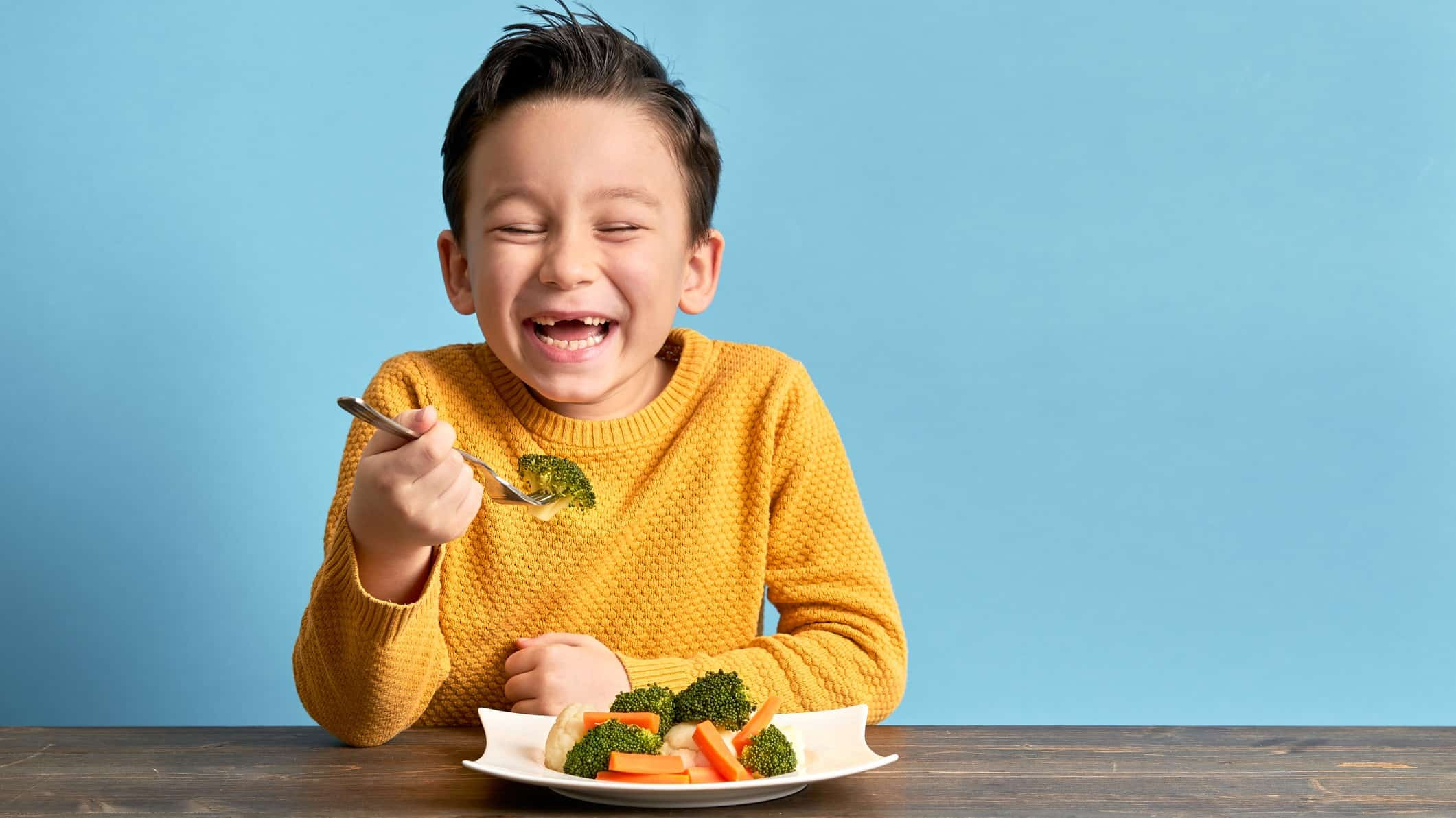 happy child eating healthy food from a bowl with fork in hand