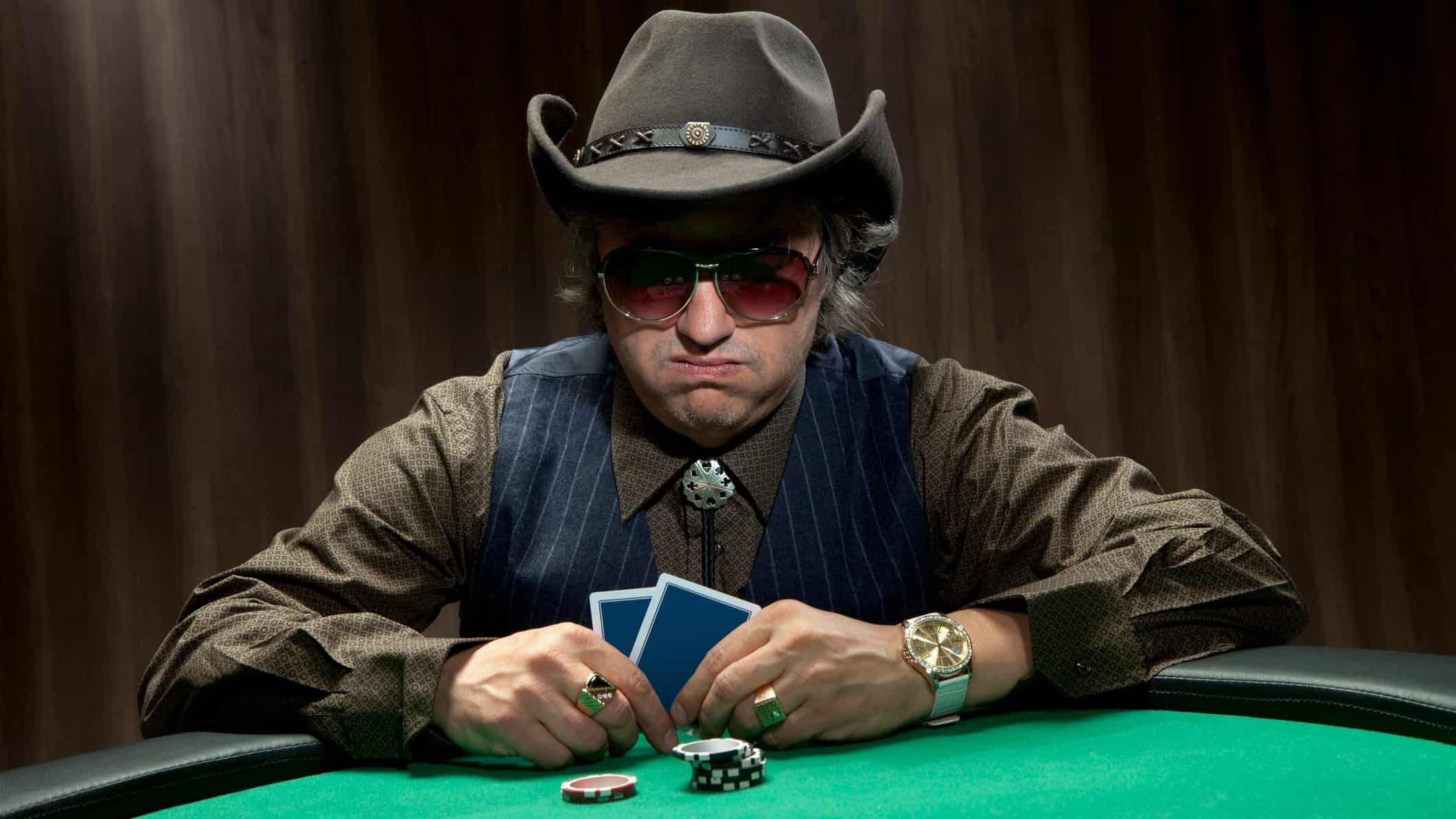 Man in hat at casino table with cards and chips looking disappointed