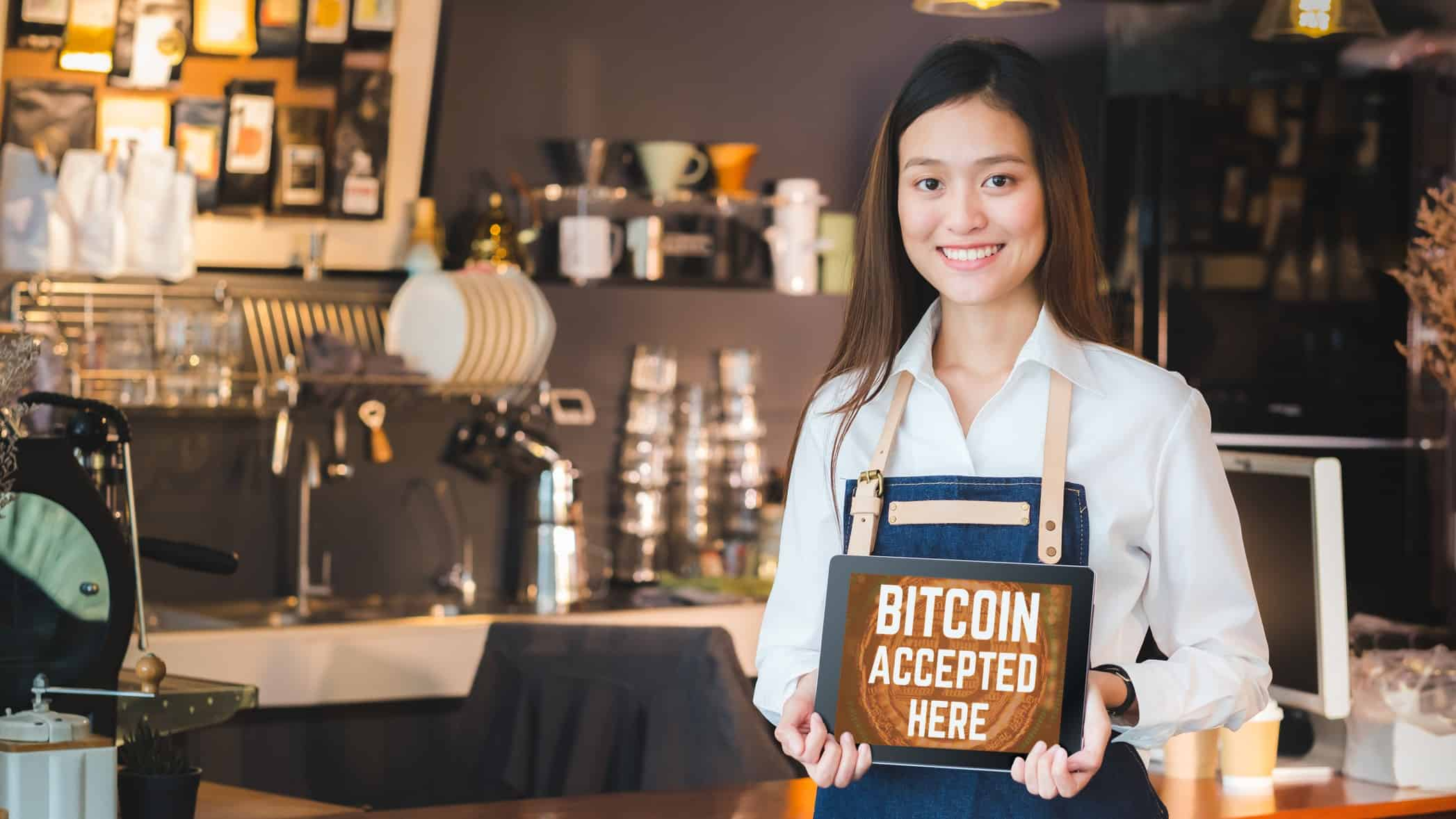 A young woman working in a coffee shop holds a sign saying: 'Bitcoin accepted here'