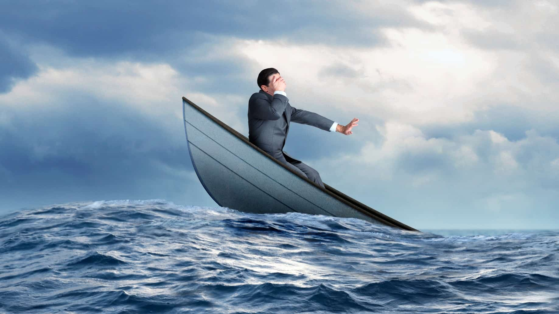 Businessman puts hand over eyes on a sinking boat in ocean