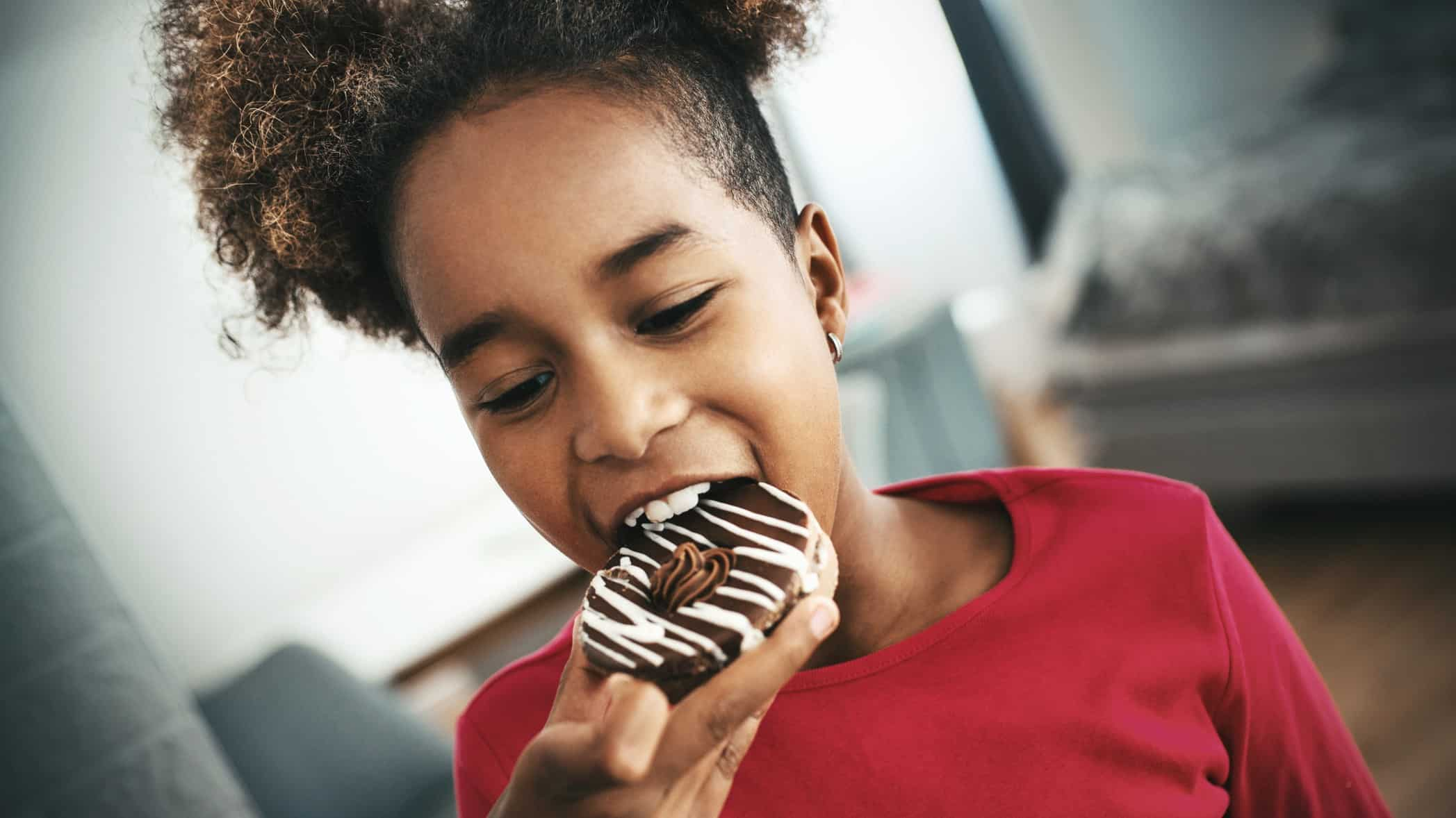 Young black girl taking a big bite out of a chocolate doughnut and she's happy about it