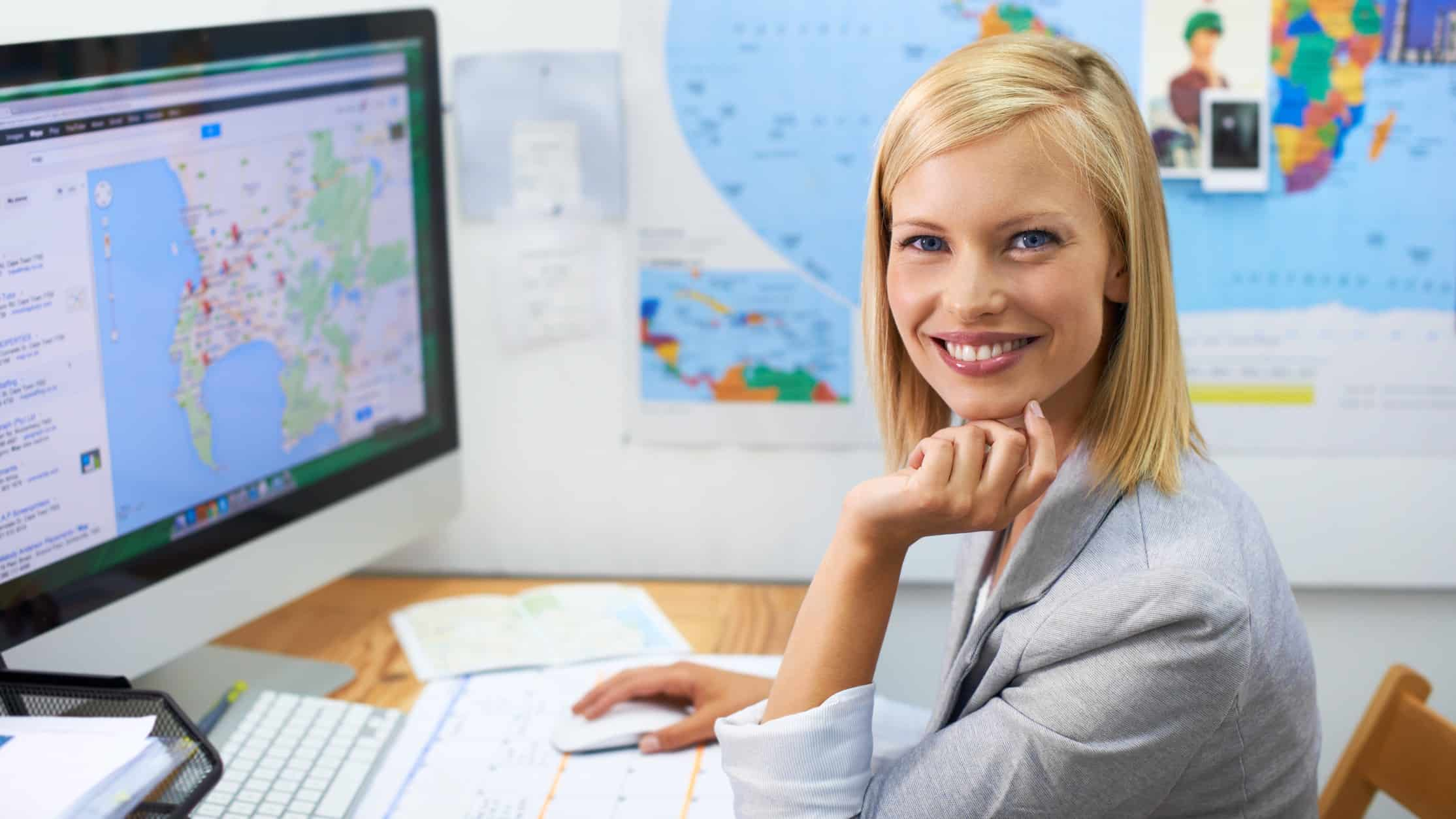 A smiling travel agent sitting at her desk working for Flight Centre