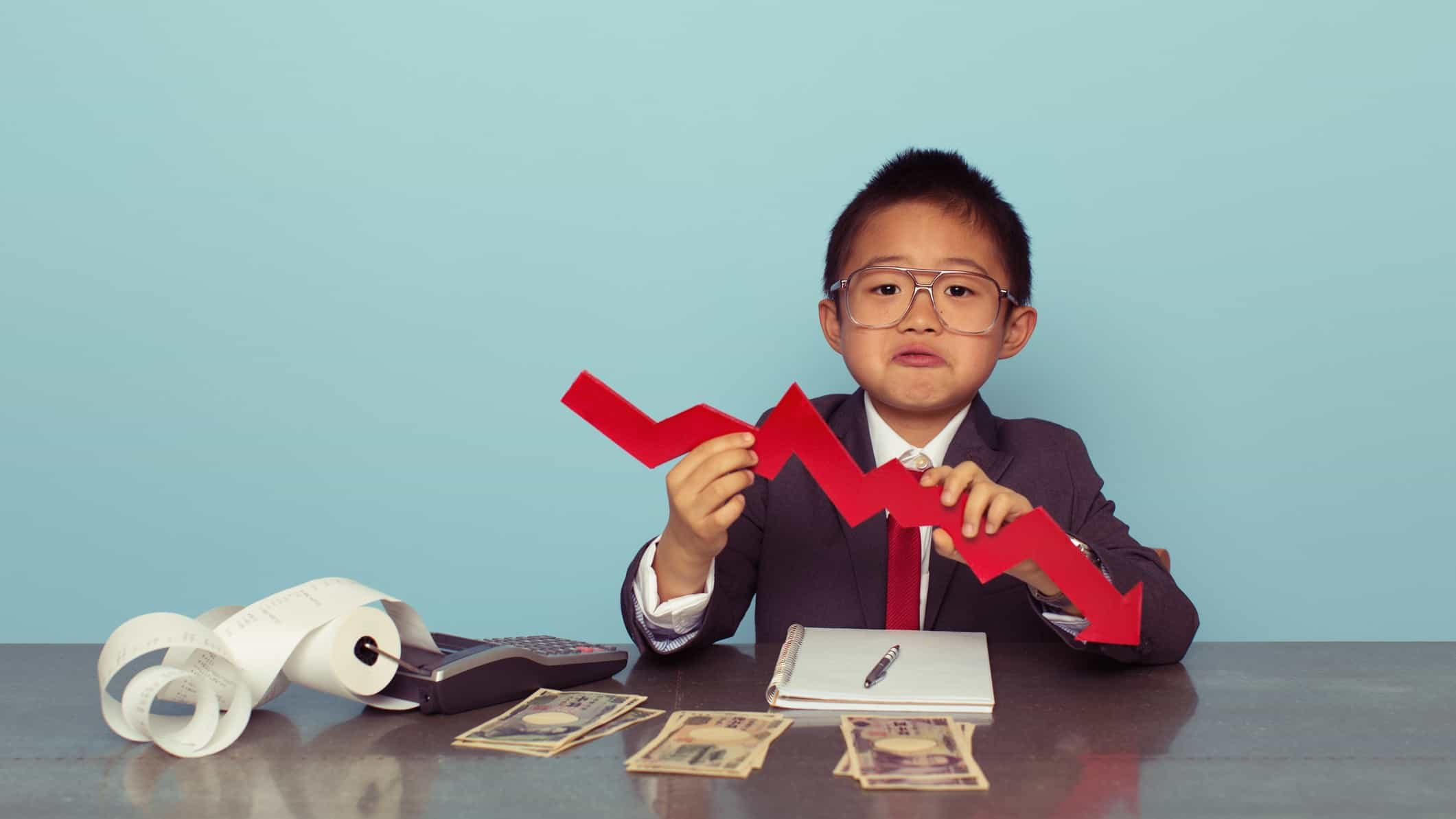 A child in full business suit holds a falling, zigzagged red arrow pointing downwards while sitting at a desk that holds cash and an old-fashioned adding machine with paper spooling.