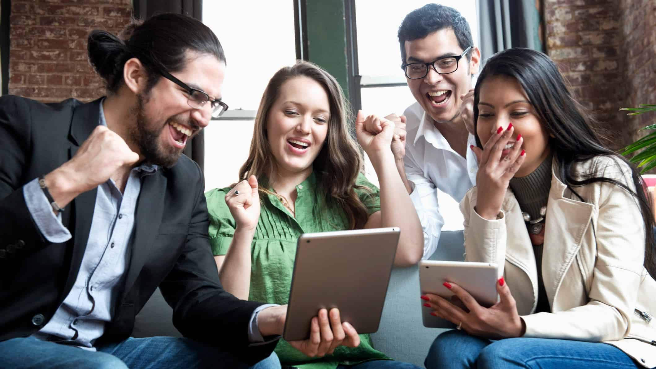 Group of people cheer around tablets in office