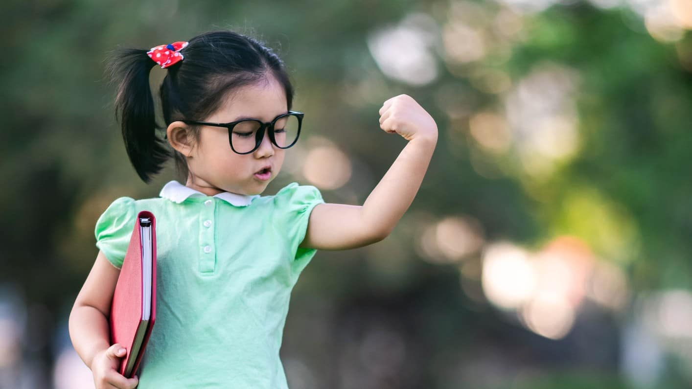 Young girl wearing glasses flexes her left bicep confidently.