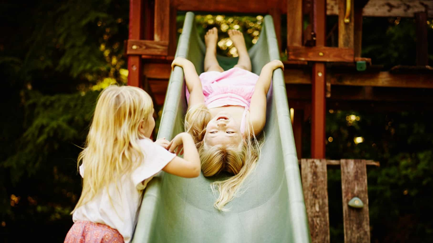 A young girl stands by the slide in a playground while her friend slides down head first and on her back.