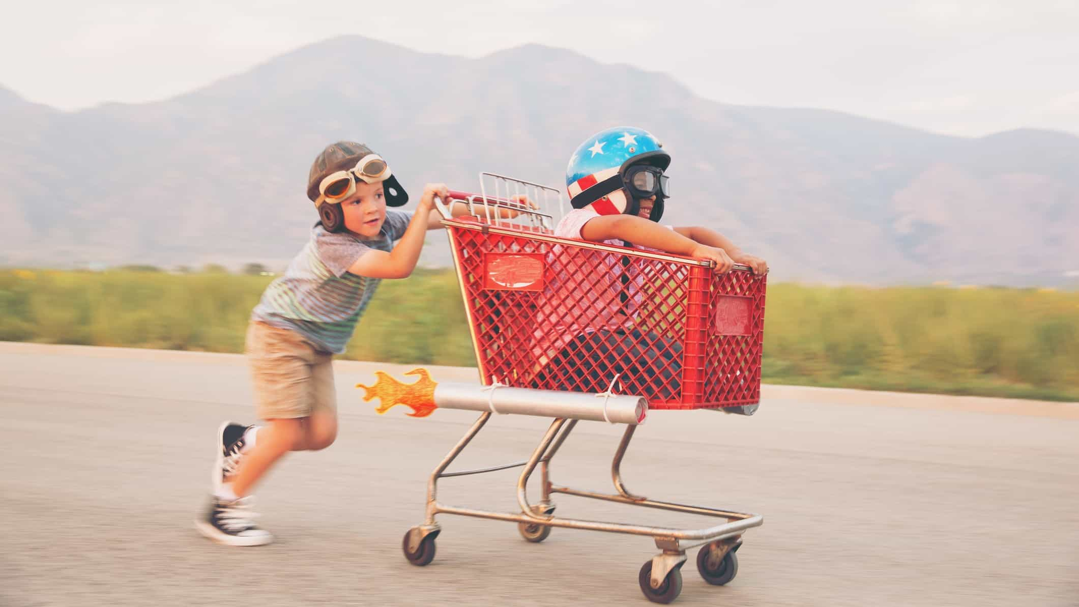A young boy pushing his friend in a shopping trolley race along the road.