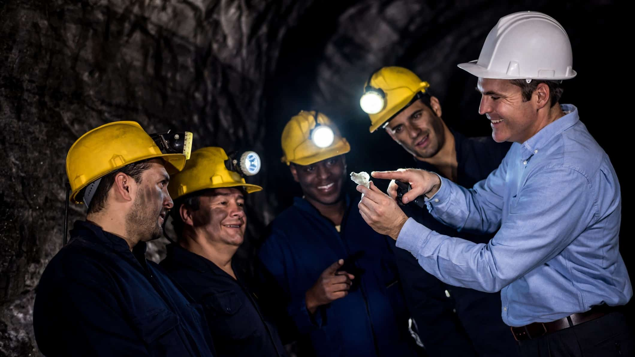 happy miners looking at piece of iron ore in underground mine