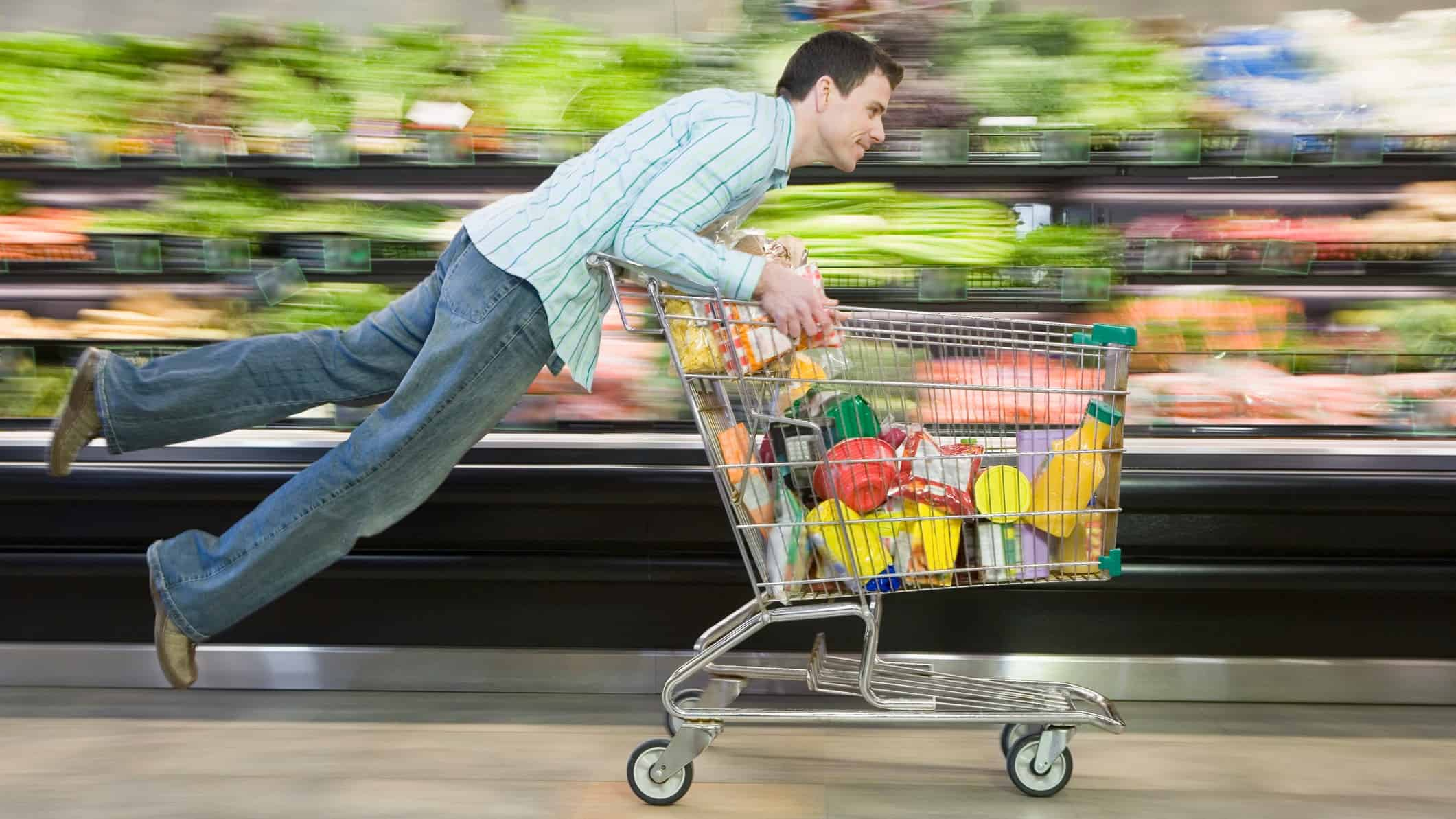 Man racing shopping trolley through supermarket likes coles or woolworths