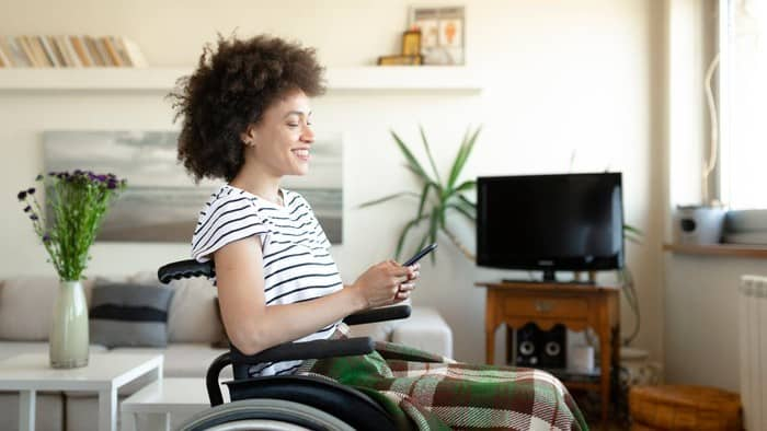 woman in wheelchair happy while investing online
