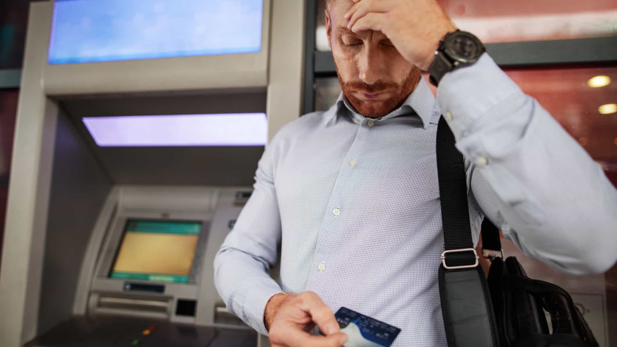 man looking stressed at ATM
