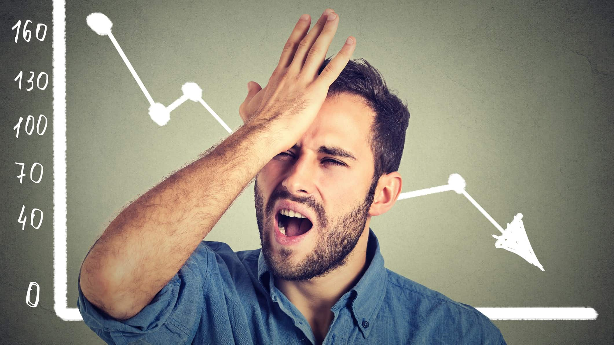 A man stands in front of a chart with an arrow going down and slaps his forehead in frustration.