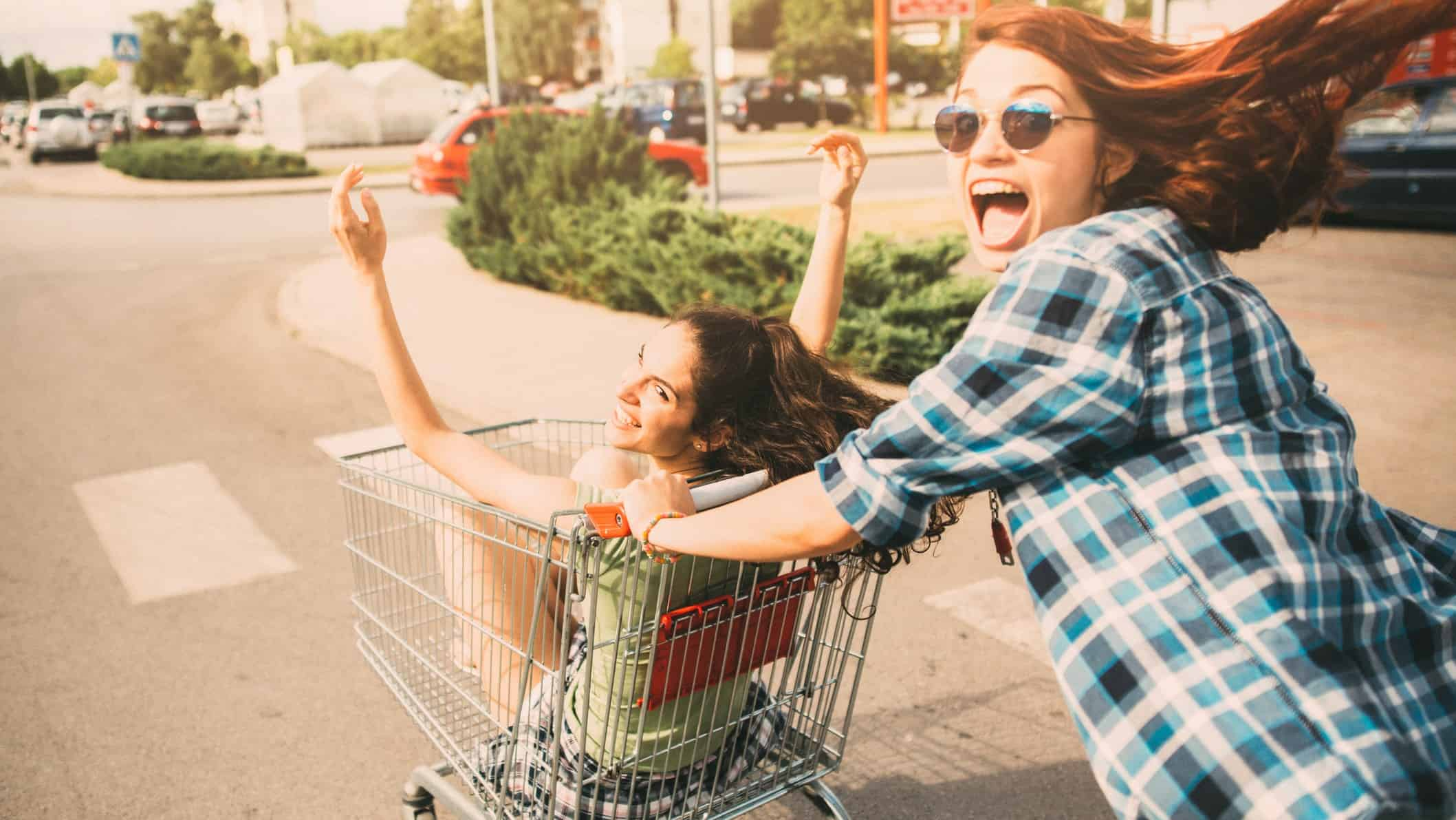 A laughing woman pushes her friend in a supermarket trolley