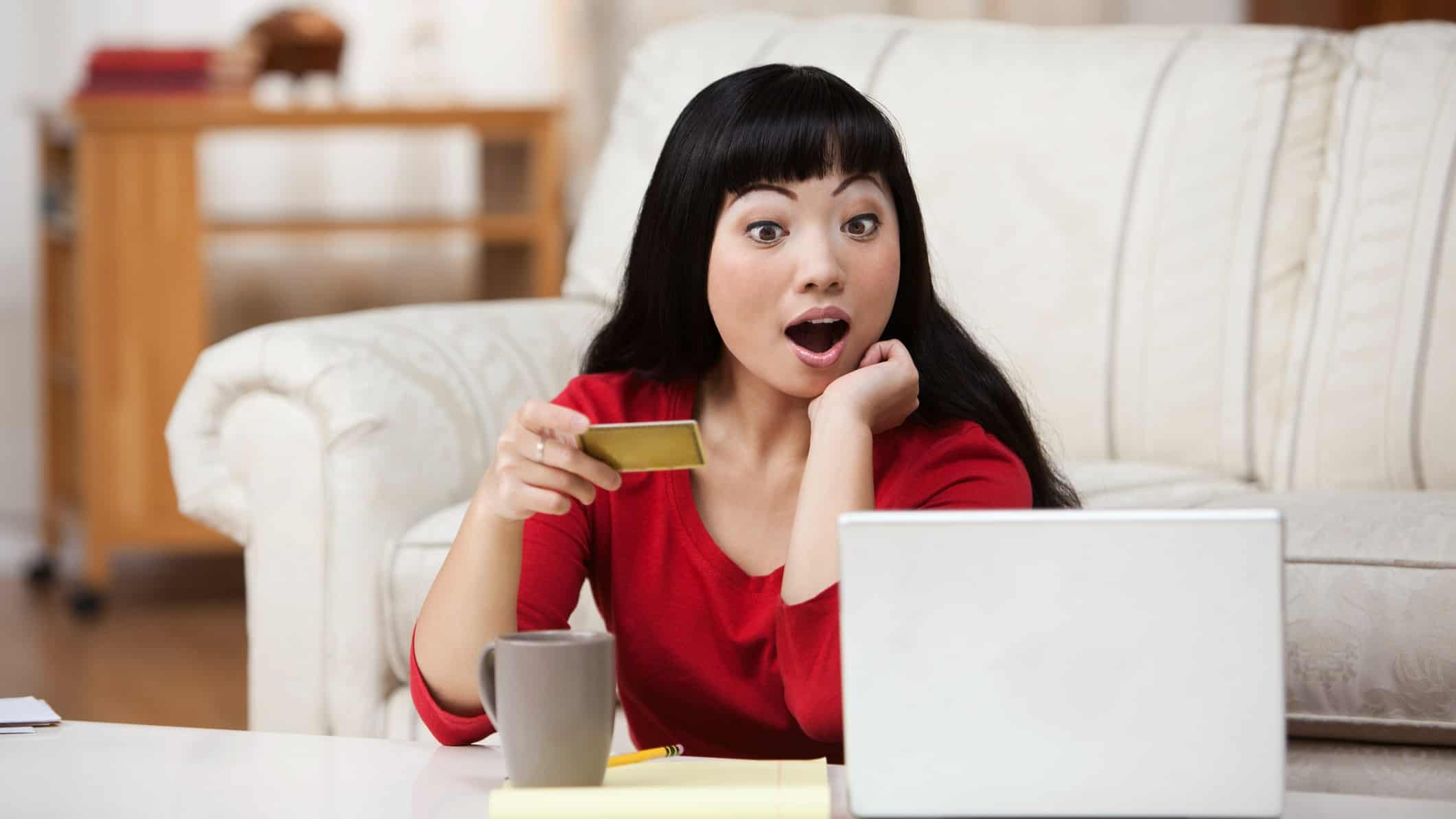 surprised shopper, unexpected news, person at computer with payment card,