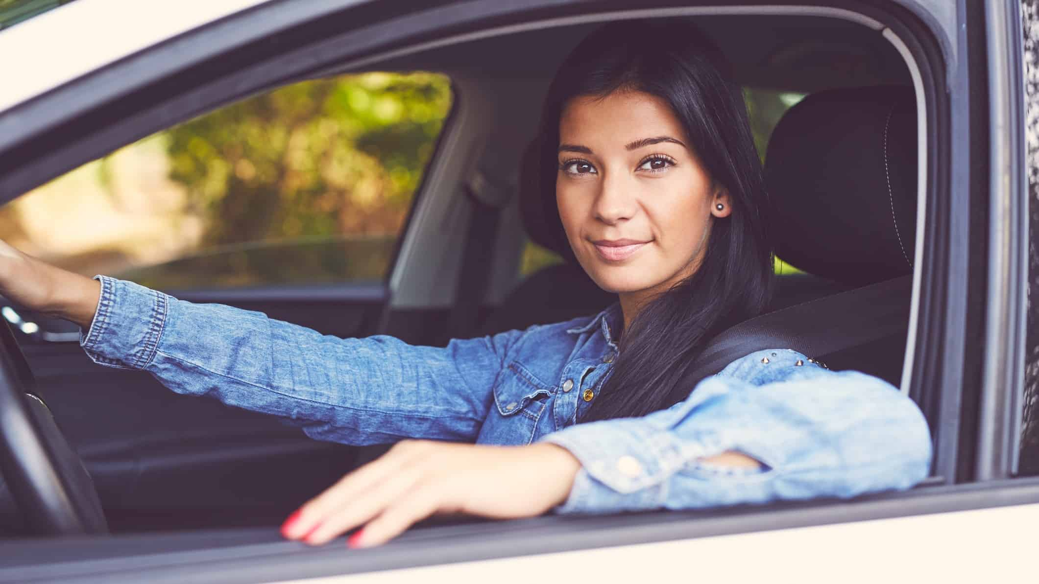 a woman sits in the driver's seat of a car with her arm resting on the door with a small smile on her face, looking out of the car.