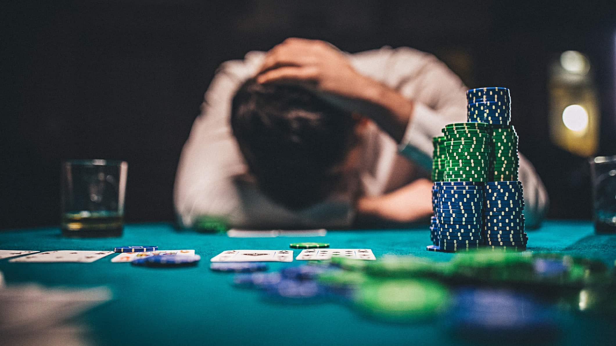 a sad gambler slumps at a casino table with hands on head and a large pile of casino chips in the foreground.
