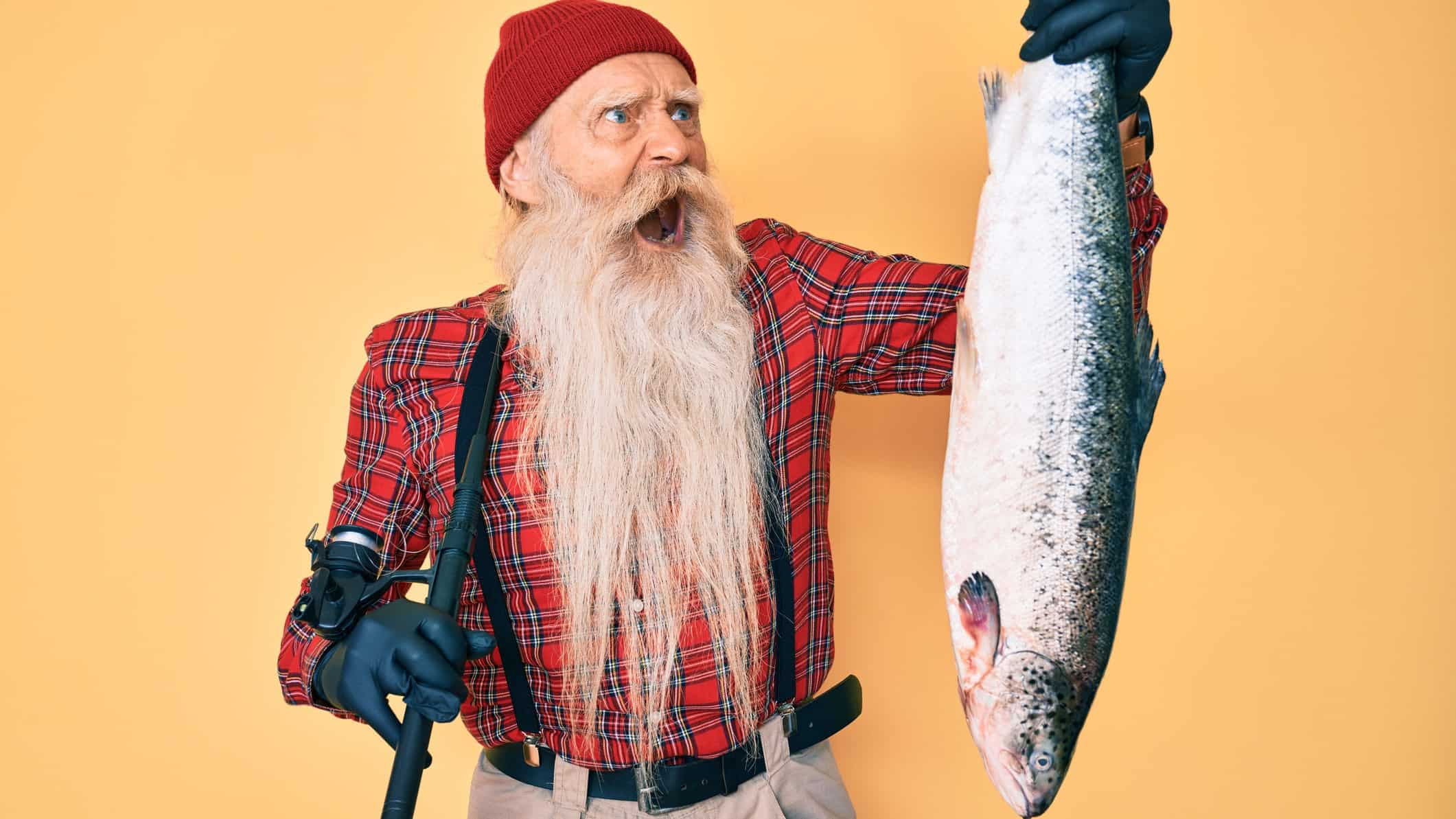 a fisherman with a long beard makes a crazy widemouthed face at a large salmon held by the tail in one of his hands.