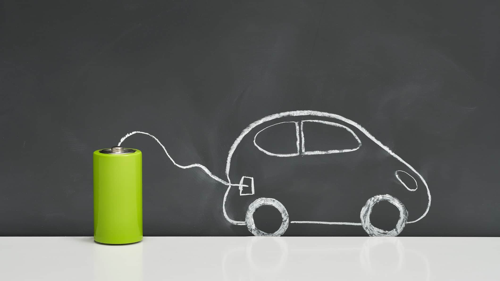 a chalk drawing of a car is connected to a real green battery, signifying clean energy