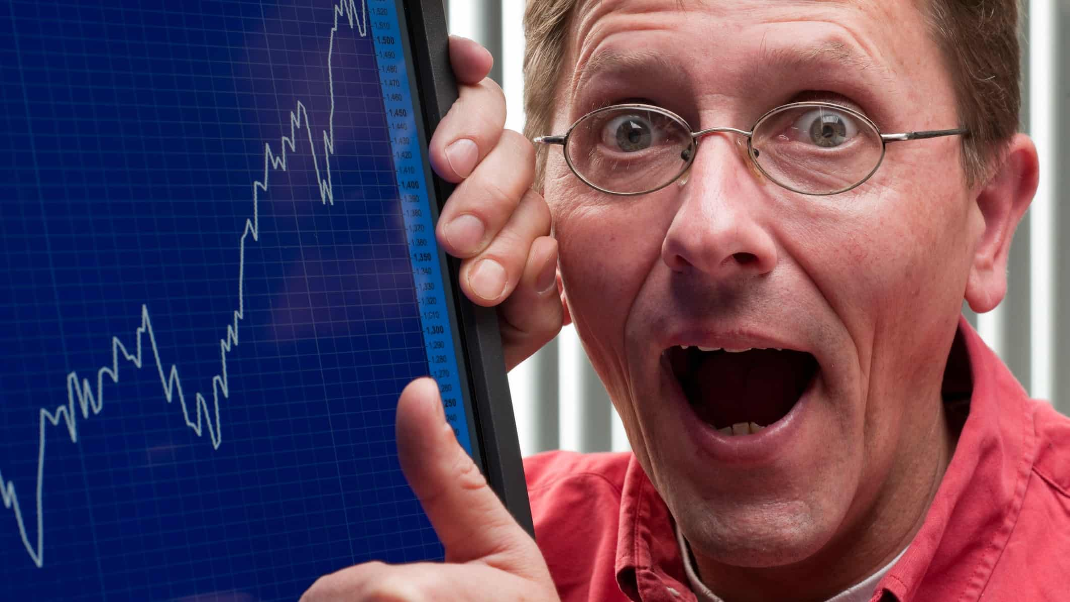a happy investor with wide mouth expression grasps a computer screen that shows a rising line charting the upward trend of a share price