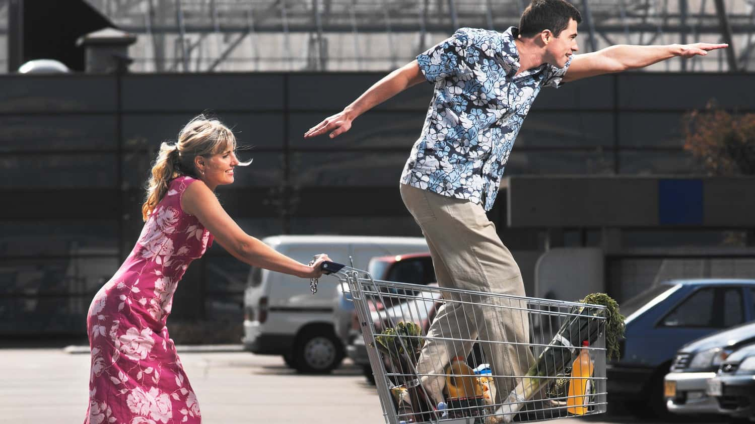 a woman pushes a man standing in a shopping trolley pointing ahead far off into the distance.
