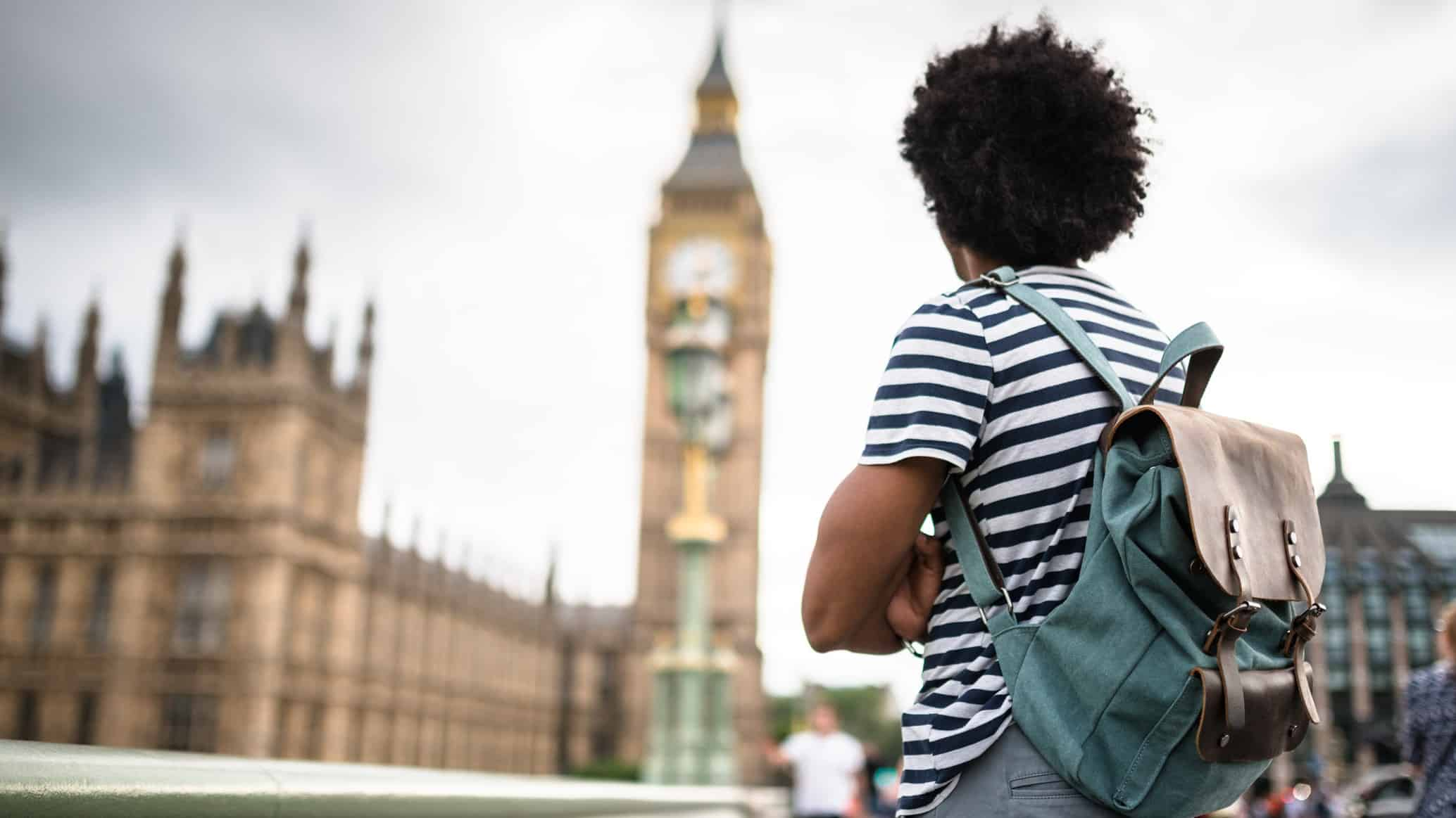 a backpacker stands looking at big ben in London.
