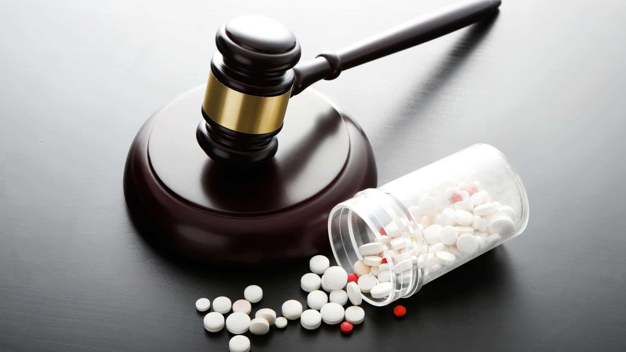 a legal gavel rests near a bottle of pharmaceutical pills with the contents spilling onto the desk.