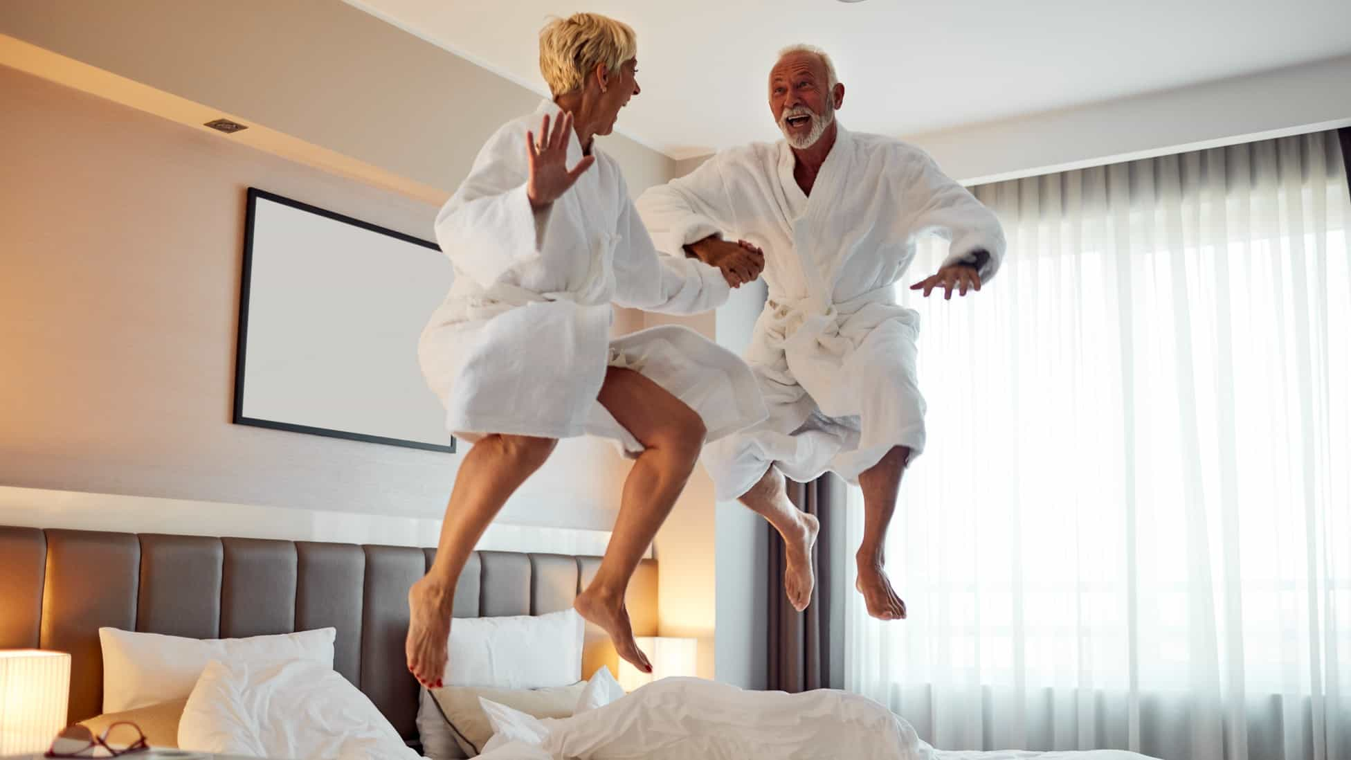 An older couple in white robes jump on their bed with joyous faces, thrilled about the good news.