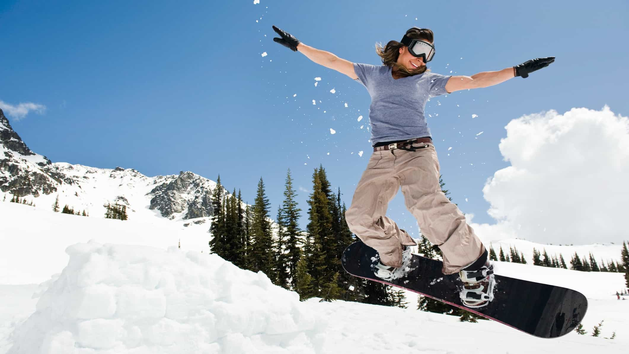 Female snowboarder flies high in the clouds.