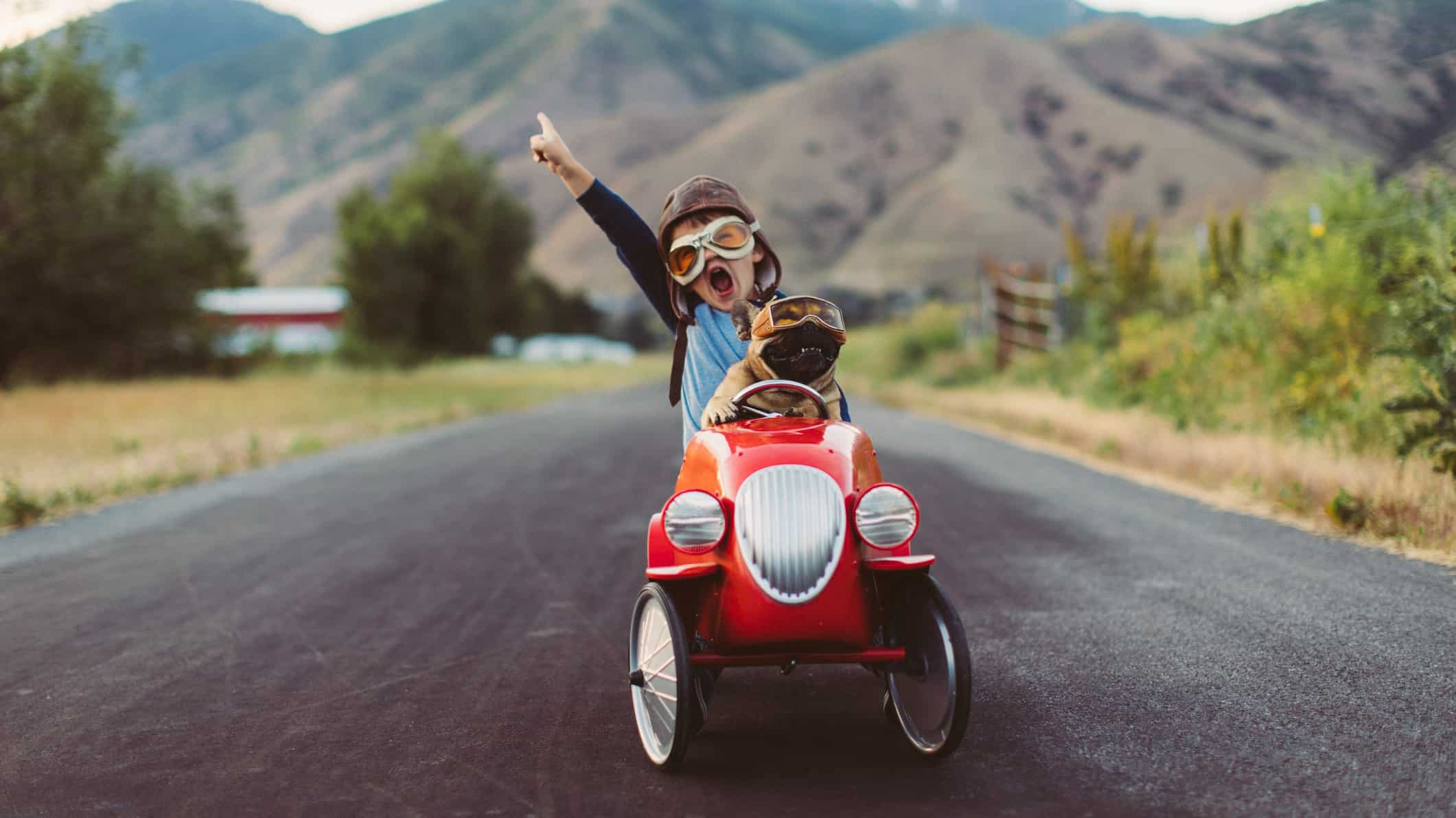 a child in a billy cart style car holds a hand in the air as he drives ahead on an open road.