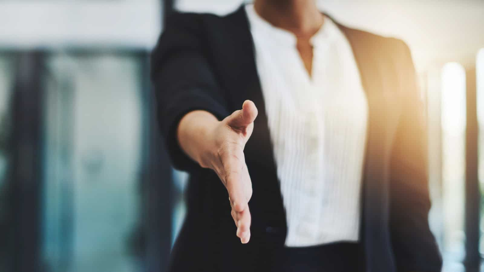 businesswoman holds hand out to shake
