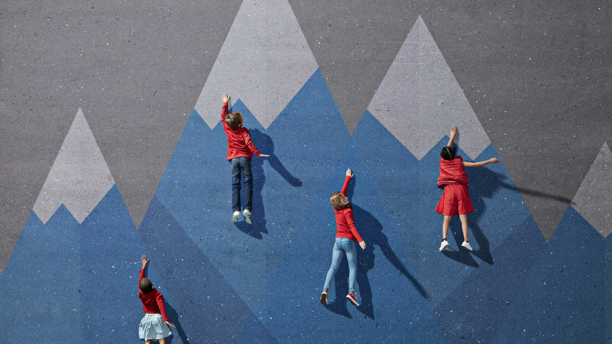 Four children climbing up a wall at different stages